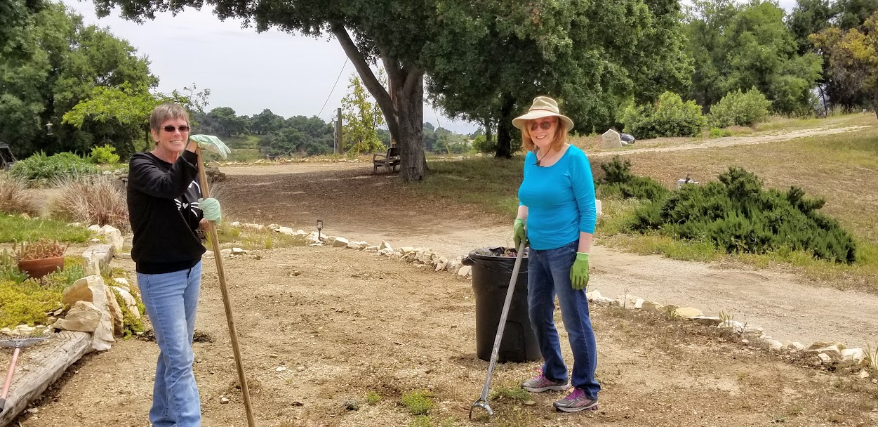 WEEDING THE GARDEN by the Visitor Center at Meher Mount are volunteers Susie Lemieux and Erin Sommerville. (Photo: Margaret Magnus, May 18, 2019)