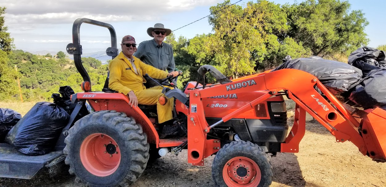 OFF TO MOW some of the more remote access fields of Meher Mount that are near the homes of Meher Mount's neighbors. Ray Johnston, driving the tractor, and Sam Ervin. (Photo: Margaret Magnus, May 20, 2019)