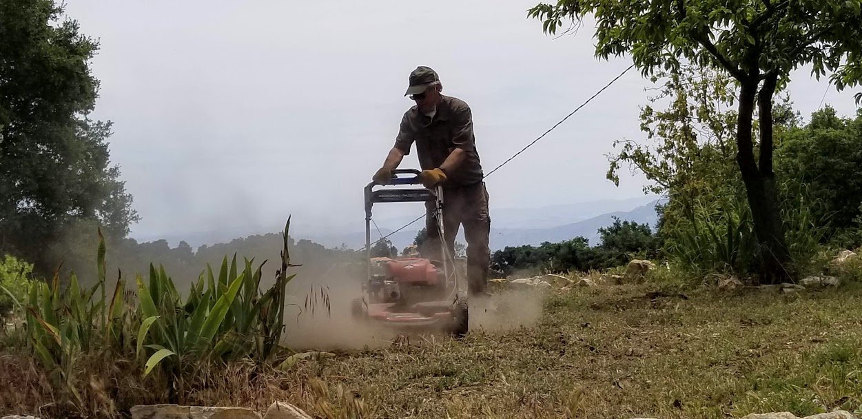 BING HECKMAN is mowing the grassy area near the Visitor Center. (Photo: Margaret Magnus, May 18, 2019)