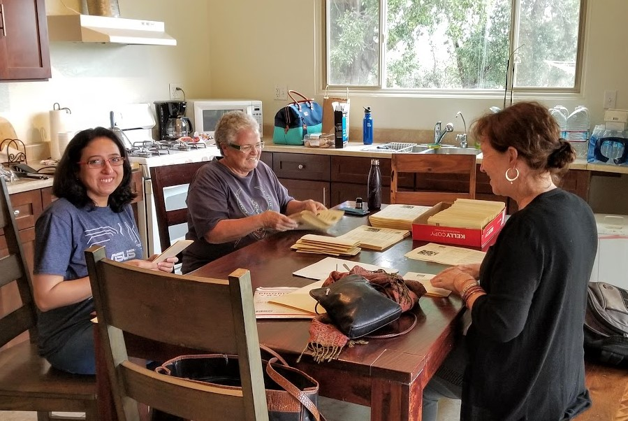 FLYERS FOR THE 2019 ANNIVERSARY SAHAVAS at Meher Mount are being folded, stamped and addressed by (left to right) Khushnam Crawford, Cassandra Bramucci, and Cynthia Griffin. (Photo: Margaret Magnus, May 18, 2019)