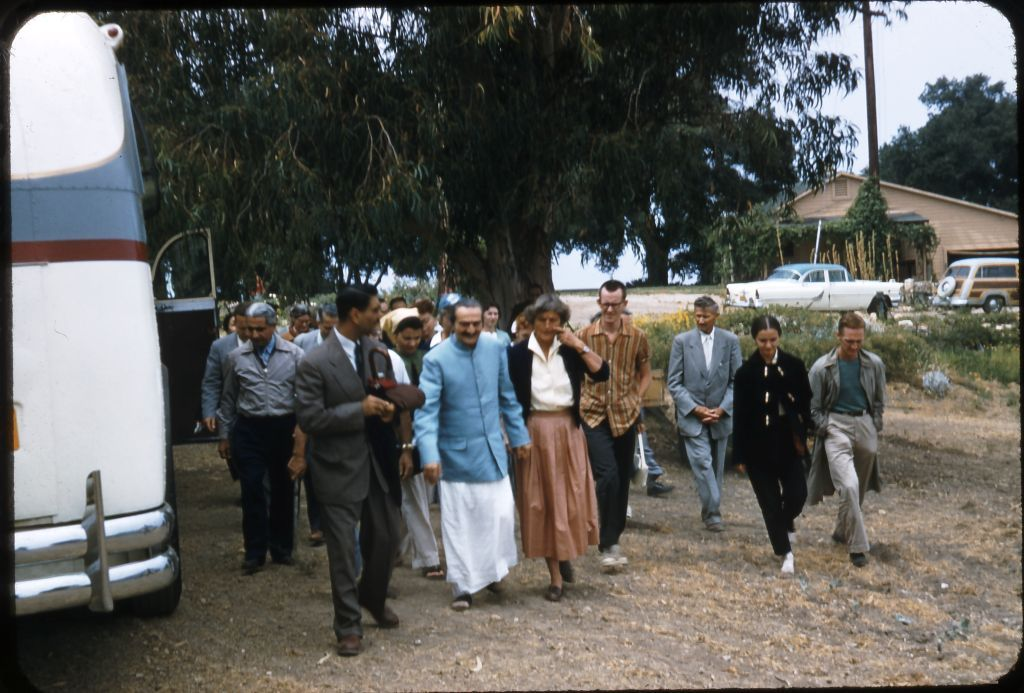 AVATAR MEHER BABA with His followers at Meher Mount on August 2, 1956. The building in the background was a farmhouse and garage on the property, which burned in 1985. In the picture are: (Left to right): Adi K. Irani (light grey jacket); Eruch Jessawala (dark suit); Bili Eaton (light scarf); Meher Baba (blue coat); Agnes Baron (orange skirt); Tex Hightower (striped shirt); Frank Hendrick (light grey suit); Marie Adair (black suit and pants); and Peter Saul (green shirt). Agnes Baron drove Meher Baba to Meher Mount in the 'Woody' station wagon pictured in the background while many of His followers traveled by bus. (Photo: Darwin Shaw, ©Meher Nazar Publications)