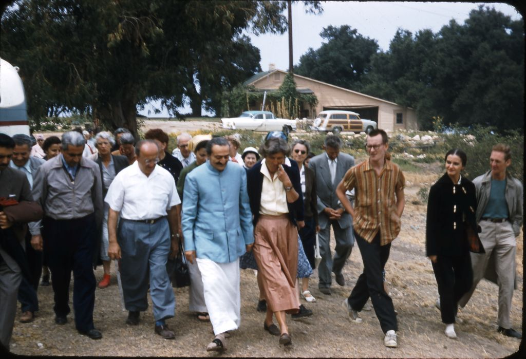 AVATAR MEHER BABA and Agnes Baron (right) at Meher Mount on August 2, 1956. Also pictured (left to right) Eruch Jessawals, Adi K. Irani, Enid Corfe (gray hair), Fred Winterfeldt (white shirt), Bili Eaton (light scarf), Jeanne Shaw (white hat), Frank Hendrick (grey suit), Tex Hightower (striped shirt),Marie Adair (in black), and Peter Saul (green shirt). (Photo: Darwin Shaw, ©Meher Nazar Publications)