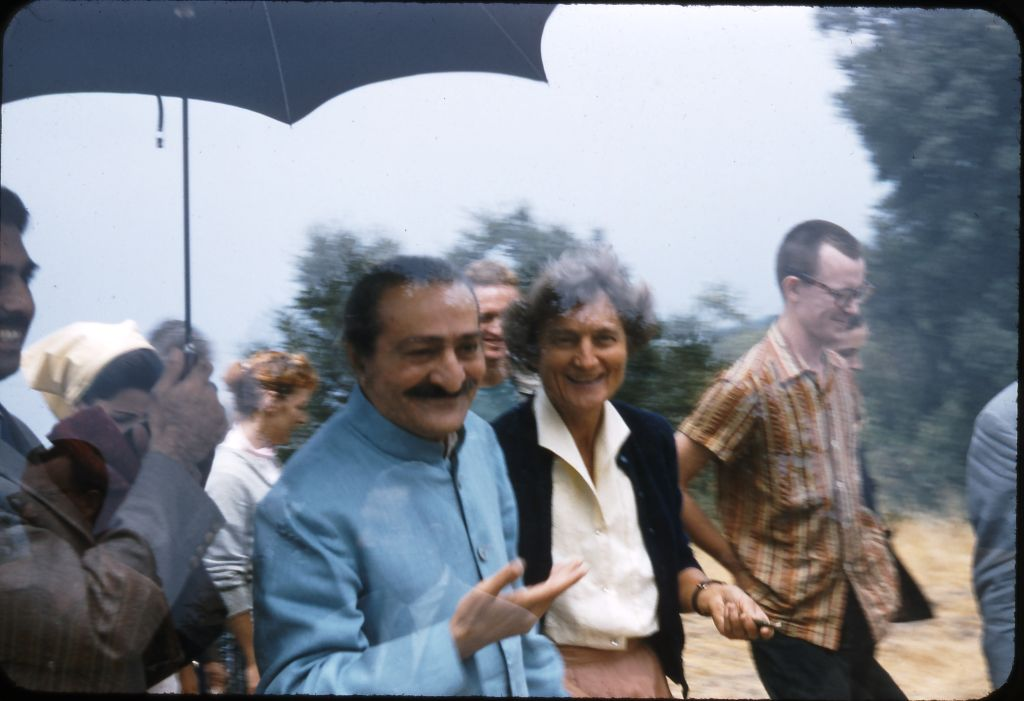 AVATAR MEHER BABA and Agnes Baron at Meher Mount on August 2, 1956. Agnes, a co-founder and lifetime caretaker of Meher Mount, is clearly delighted — long after the shock and sorrow of Meher Baba's auto accident en route to Meher Mount four years earlier — that Meher Baba has finally arrived at Meher Mount. Close disciple Eruch Jessawala is holding the umbrella, and Tex Hightower, one of the dancers who studied with Margaret Craske (a close Western disciple), is in the striped shirt. (Photo: Darwin Shaw, ©Meher Nazar Publications)