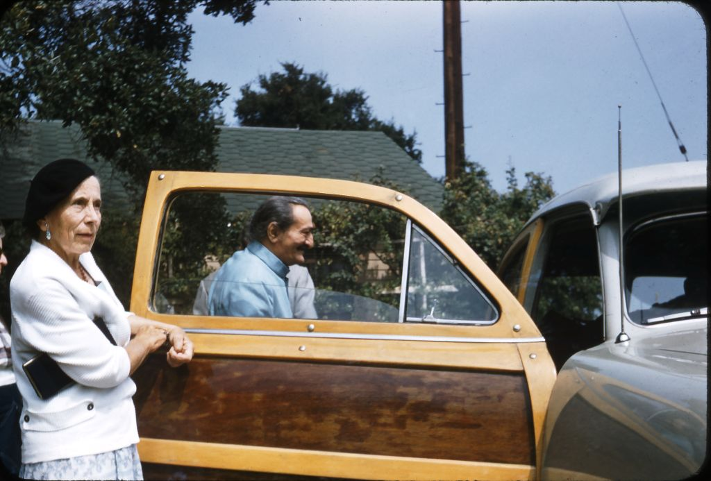 AVATAR MEHER BABA entering the 'Woody' driven by Agnes Baron as He prepares to leave Meher Mount for the ride back to Hollywood on August 2, 1956. Pictured with Him is Kitty Davy, a close Western disciple, and one of the pillars of the Meher Spiritual Center in Myrtle Beach, SC. (Photo: Darwin Shaw, ©Meher Nazar Publications)