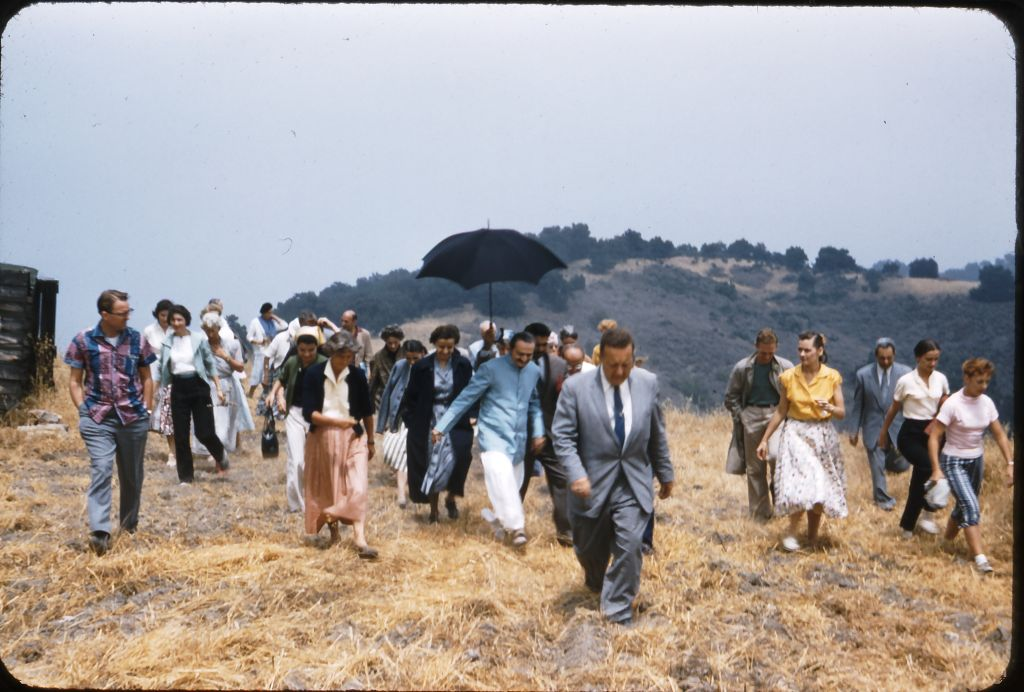 HURRYING TO KEEP UP with Avatar Meher Baba (blue coat) as He tours Meher Mount with co-founder and lifetime caretaker Agnes Baron (light orange skirt) on August 2, 1956. Lud Dimpfl is the man in the suit in front. (Photo: Darwin Shaw, ©Meher Nazar Publications)