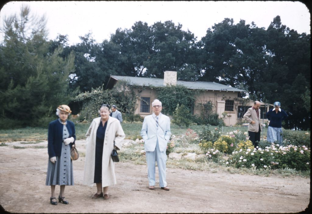 VISITORS to Meher Mount on August 2, 1956, with Avatar Meher Baba. (Left to right): Unidentified; Elizabeth Patterson, one of the founders of the Meher Spiritual Center in Myrtle Beach, SC; and Dana Field. (Photo: Darwin Shaw, ©Meher Nazar Publications)  To identify any other figures in the photograph, contact Meher Mount.