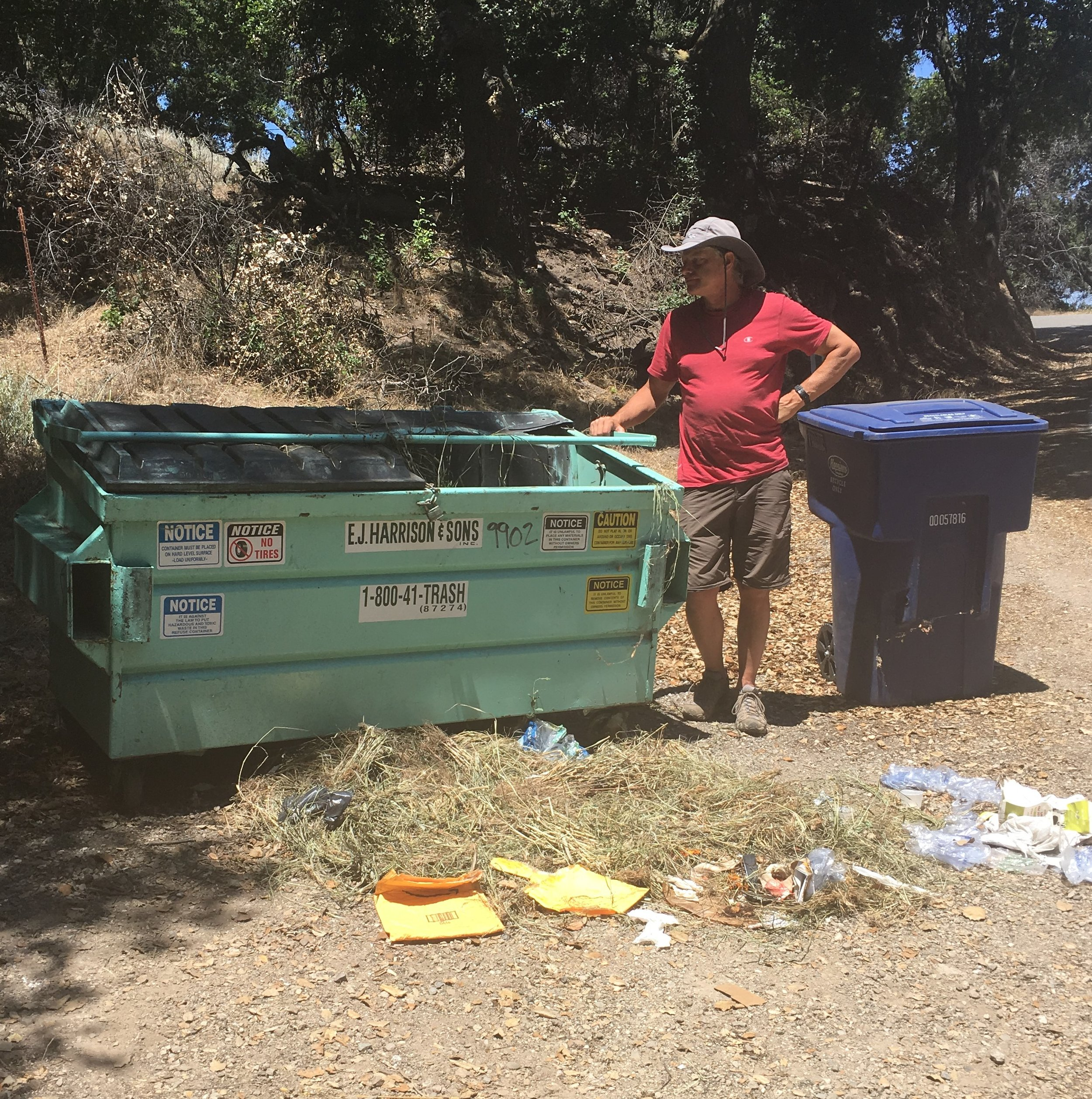 ERIC CARLSON inspects the smashed-in metal cover of Meher Mount's dumpster after a surprise visit - probably from a bear. (Photo: Ellen Kwiatkowski, July 2019)