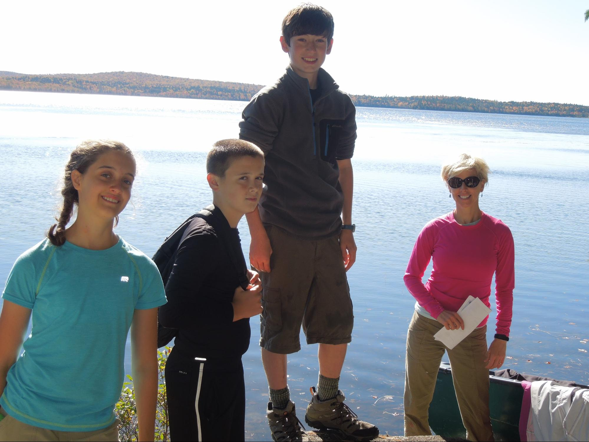 Owyn, as an HMS adolescent student, standing tall with best friend Joe, classmate Allie and guide Kim at his favorite memory place, Mount Katahdin.