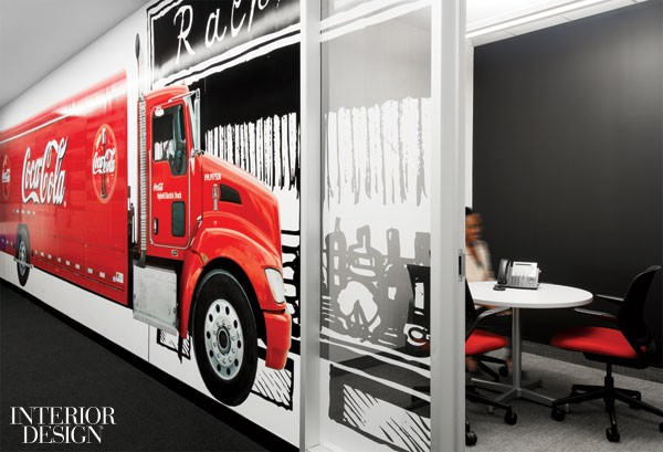 A mural of a delivery truck starts as paint on gypsum-board and ends as vinyl film on the glass front of a telephone room.