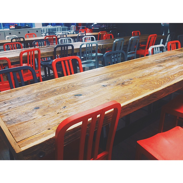 Cafeteria. Wooden tables and Coca-Cola colourway chairs. Made by  Emeco  from 111 recycled PET plastic Coke bottles