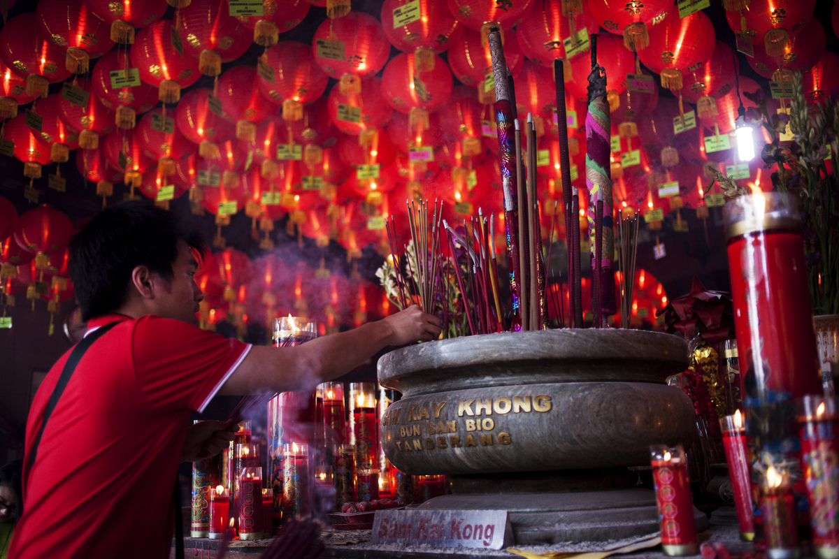 TANGERANG, INDONESIA - JANUARY 31: A man holds incense sticks as she attends prayers during Chinese New Year celebrations for the Year of The Horse at Bun San Bio Temple on January 31, 2014 in Tangerang, Indonesia. Indonesian chinese today to celebrate the Chinese New Year and welcome the Year of the Horse, with new year's day falling on January 31st. Chinese new Year is the most important festival in the Chinese calendar and is widely celebrated across Asia. (Photo by Oscar Siagian/Getty Images)