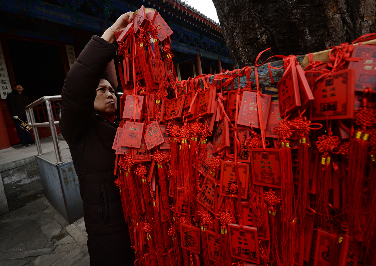 Chinese worshippers hang prayer tablets on a sacred tree at the Dongyue Temple in the hope that it brings them prosperity and good fortune for the Year of the Horse in Beijing on January 31, 2014. China welcomed in the Lunar New Year of the Horse which sees about 3.62 billion trips made by Chinese travelers during the 40-day Spring Festival travel period. AFP PHOTO/Mark RALSTON (Photo credit should read MARK RALSTON/AFP/Getty Images)