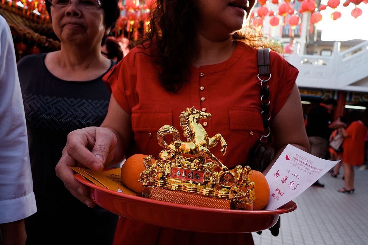KUALA LUMPUR, MALAYSIA - JANUARY 31: A Chinese ethnic holds a golden horse statue as part of her offering in Tien Hou Temple as Malaysian celebrate Chinese New Year on January 31, 2014 in Kuala Lumpur, Malaysia. Chinese New Year is traditionally celebrated from the last day on the last month of the Chinese lunisolar calendar to the Lantern Festival on the 15th day of the first month. (Photo by Rahman Roslan/Getty Images)