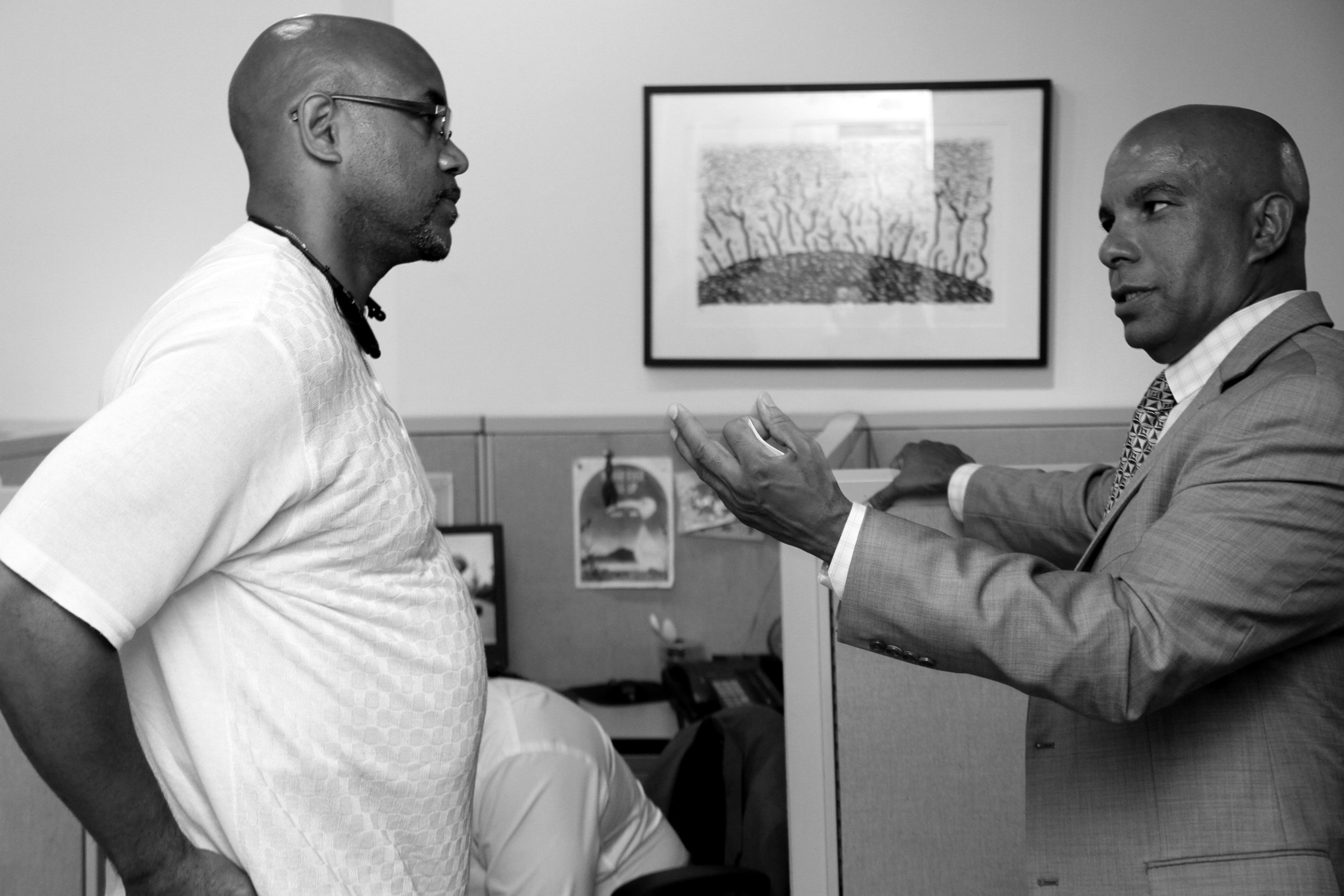 Julio Medina, our Executive Director, is pictured speaking with a close friend and community partner in our East Harlem office.