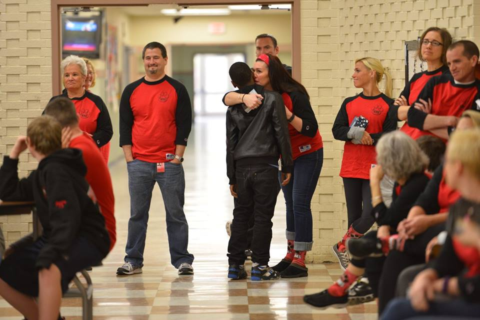 A Whitman Middle School teacher hugs a student after receiving a gesture of appreciation from him during the assembly.