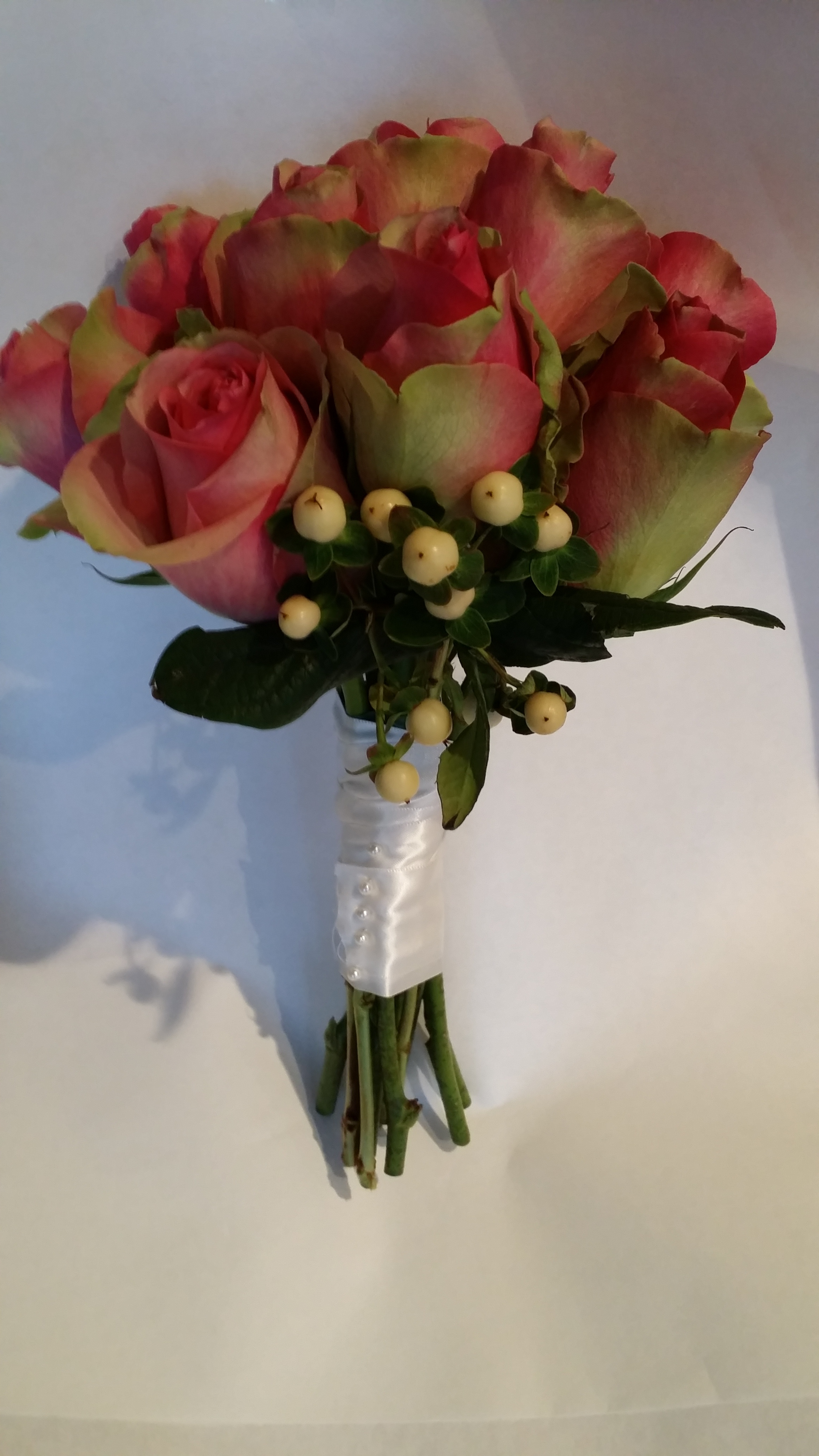 """A simple bouquet featuring """"Belleview"""" Roses, and white """"Hipericum"""" berries"""