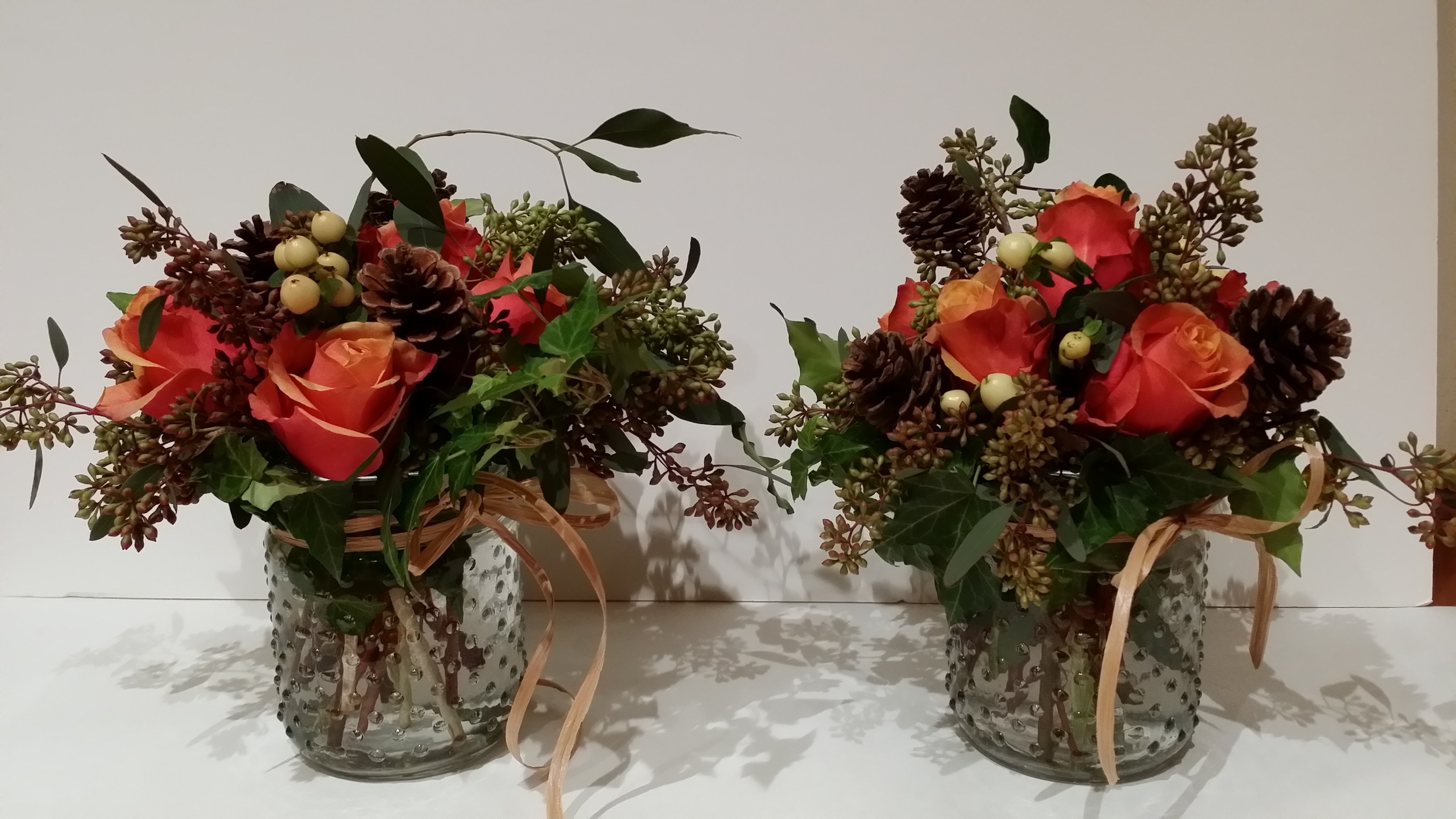 """4"""" nobbed jar with Cherry Brandy Roses, White Hipericum berries, seeded eucalyptus, and ivy. Price starting at $25.00"""