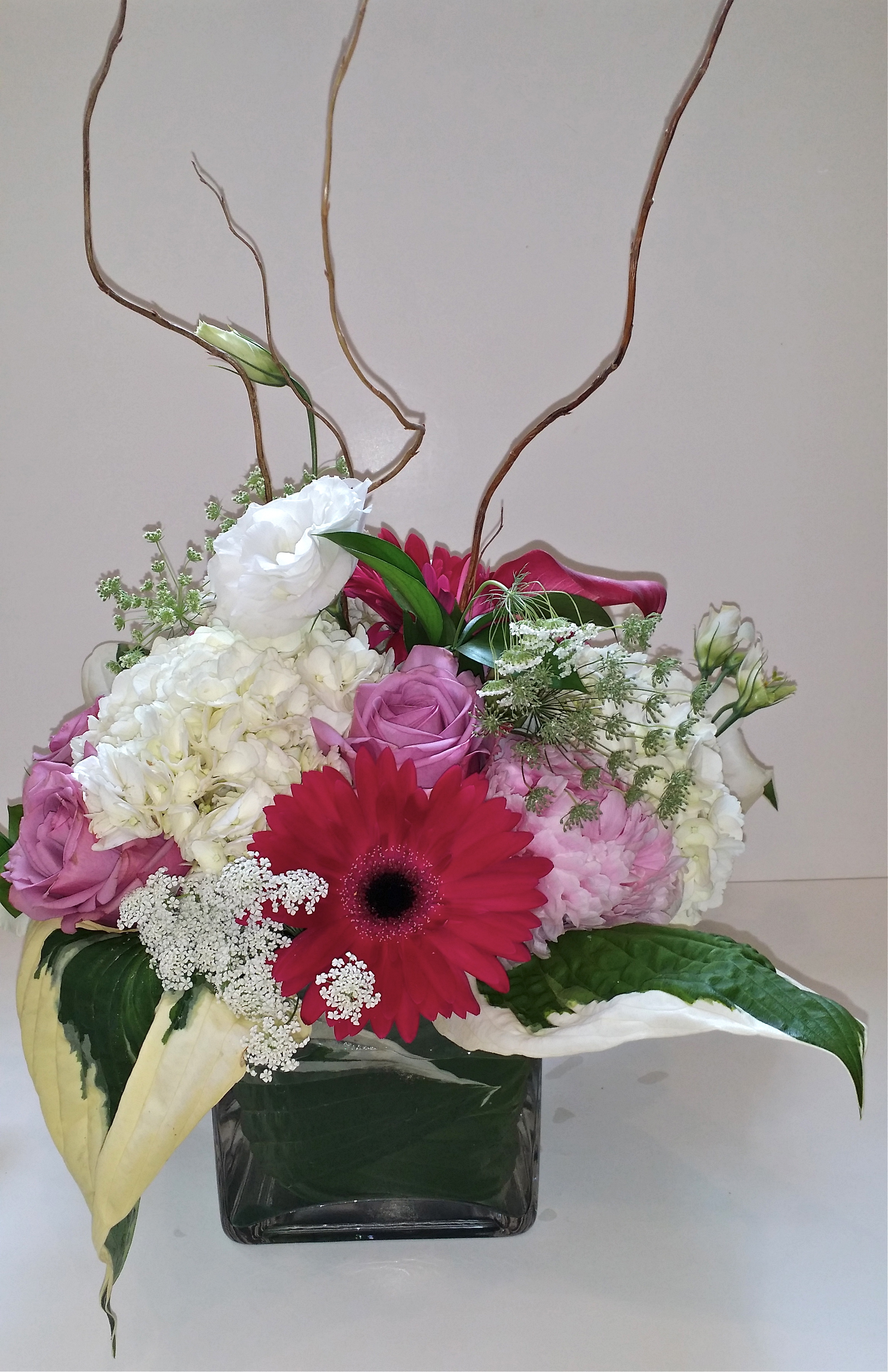 A simple arrangement for the table picks up the flowers of the Bride's bouquet.