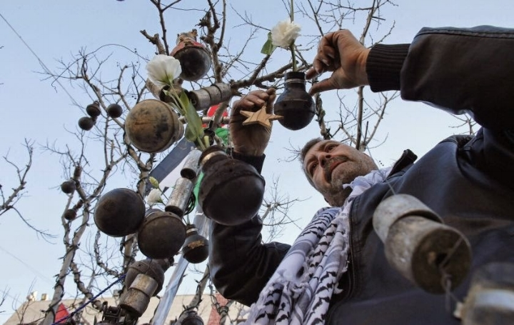 Palestinian activists decorate a sparse Christmas tree on Manger Square in Bethlehem with empty tear-gas canisters and stun grenades reportedly used on civilians by the Israeli military.