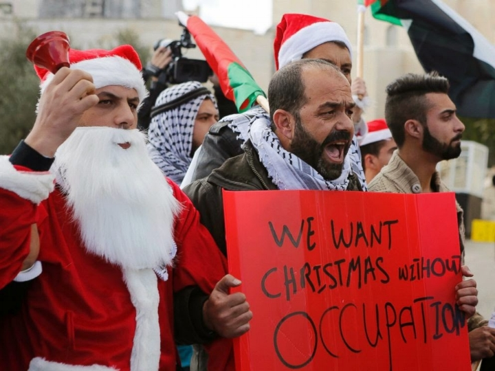 Palestinian Christians and Muslims protest during the Christmas season, in 2014, in Bethlehem.    Photo: Mussa Qawasama (2014).
