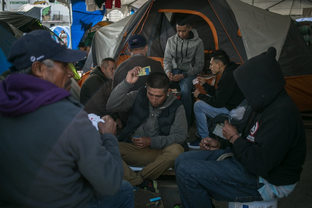 Honduran migrants play card games in a temporary shelter in Tijuana, Mexico.  Photo: The New York Times.