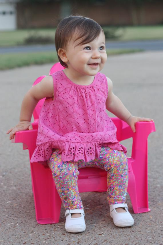 grinning in pink chair