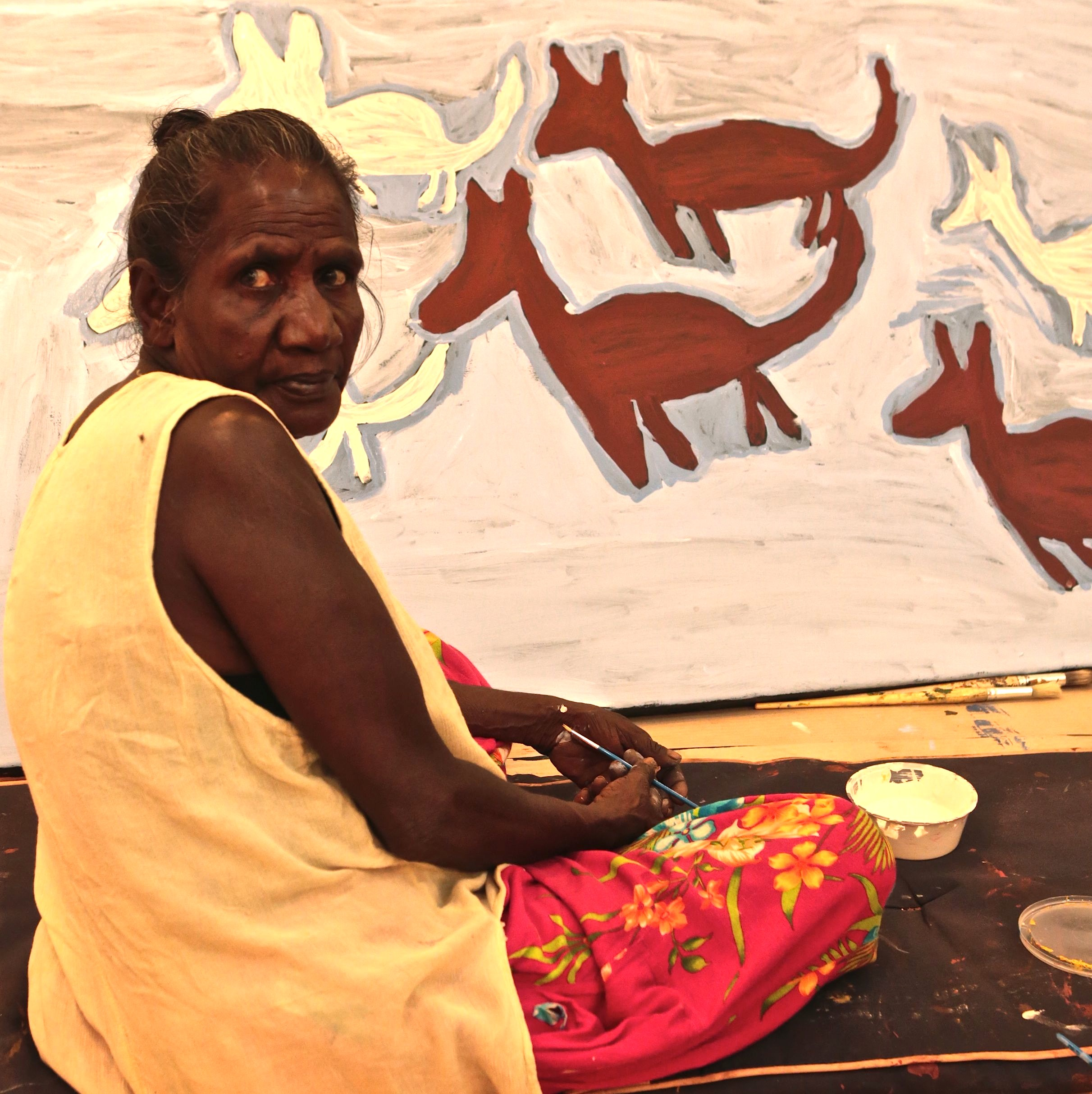 Artist Ruth Lulwarriwuy working on one of her large Dhuwa and Yirritja dog paintings.