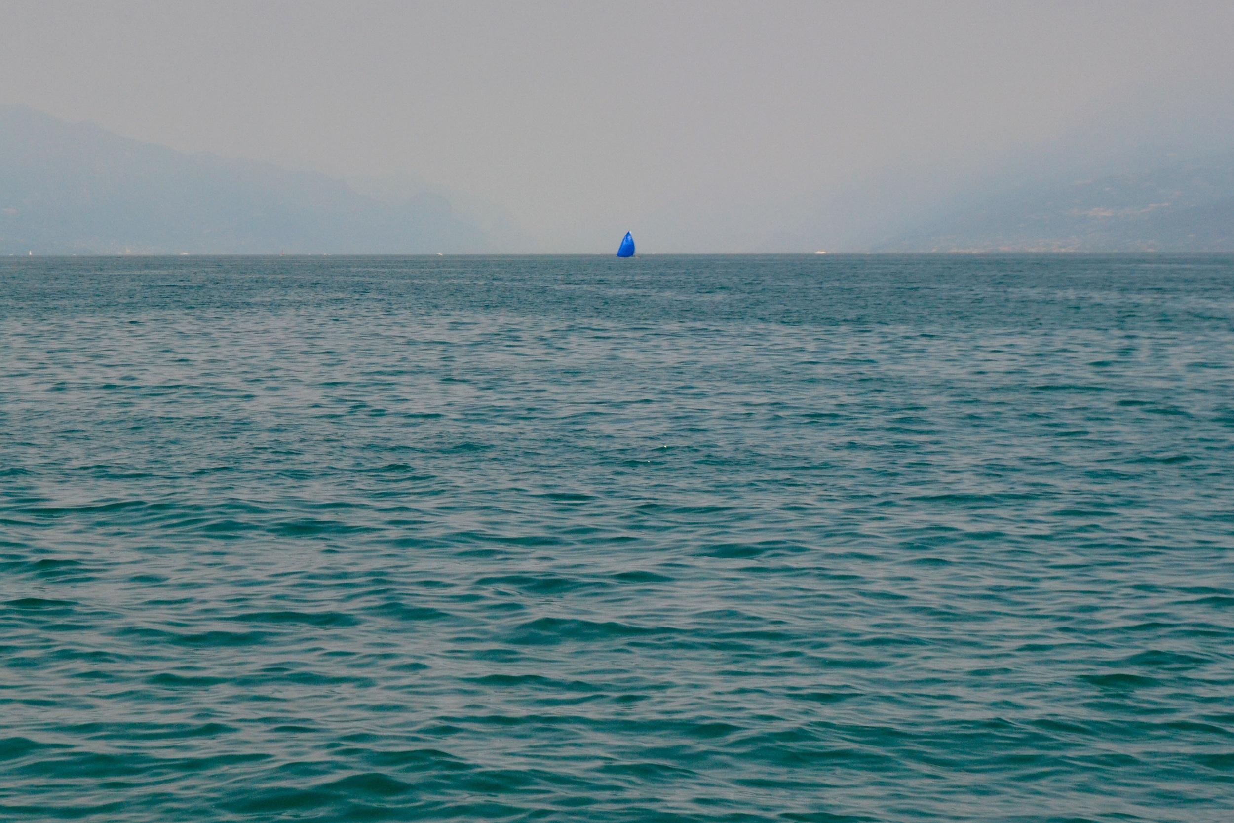 Lone blue sailboat on Lago di Garda.