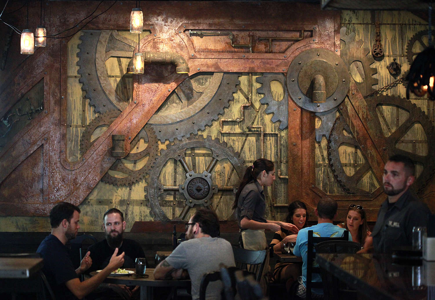 "The Mill in St. Petersburg features a ""farmhouse industrial chic"" look, according to the designer, one wall an installation of rust-freckled gears, cogs, wheels and pipes. (LARA CERRI 