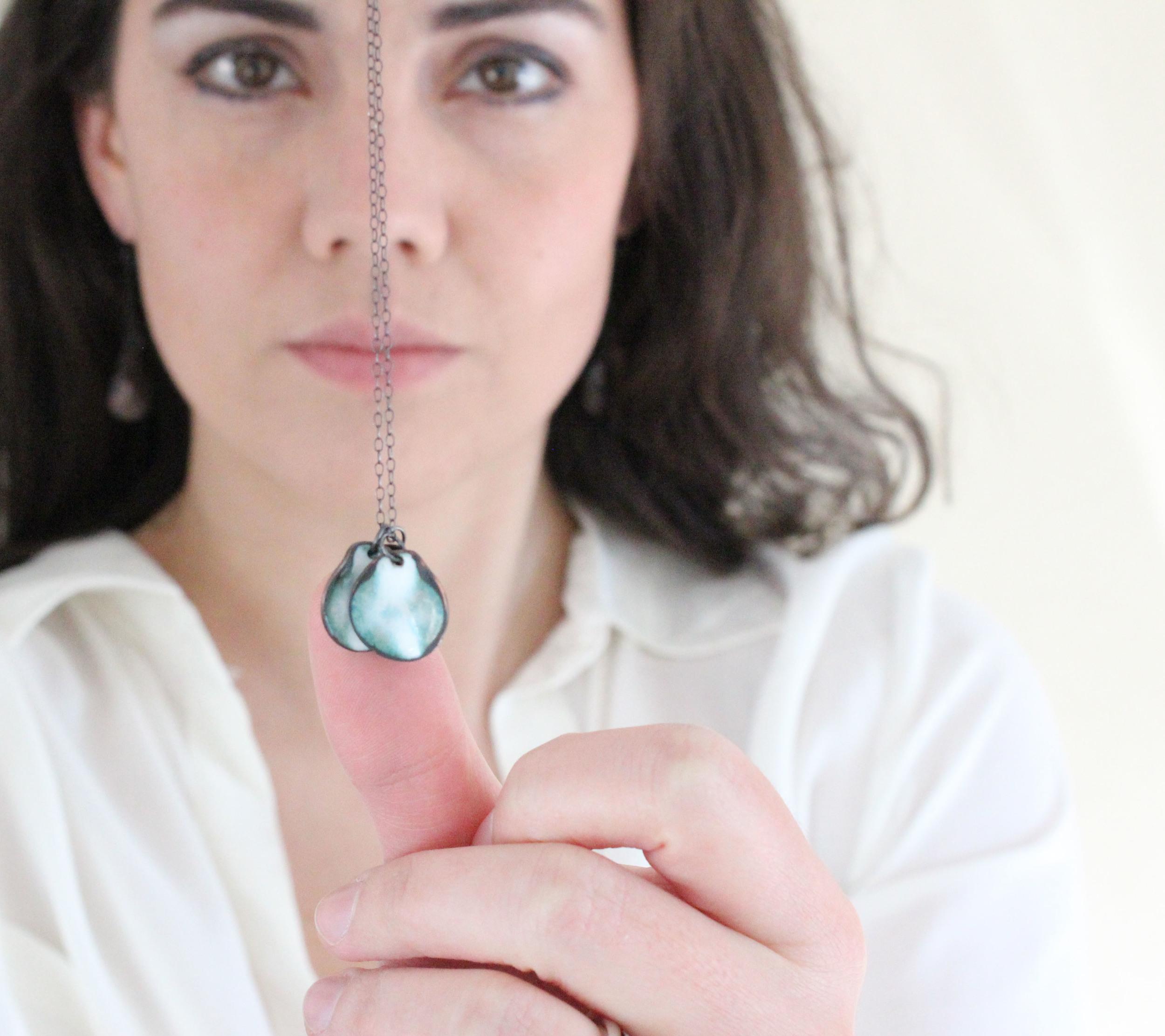 Holding the Triple Petal Necklace from the Fleur de la Mer Collection