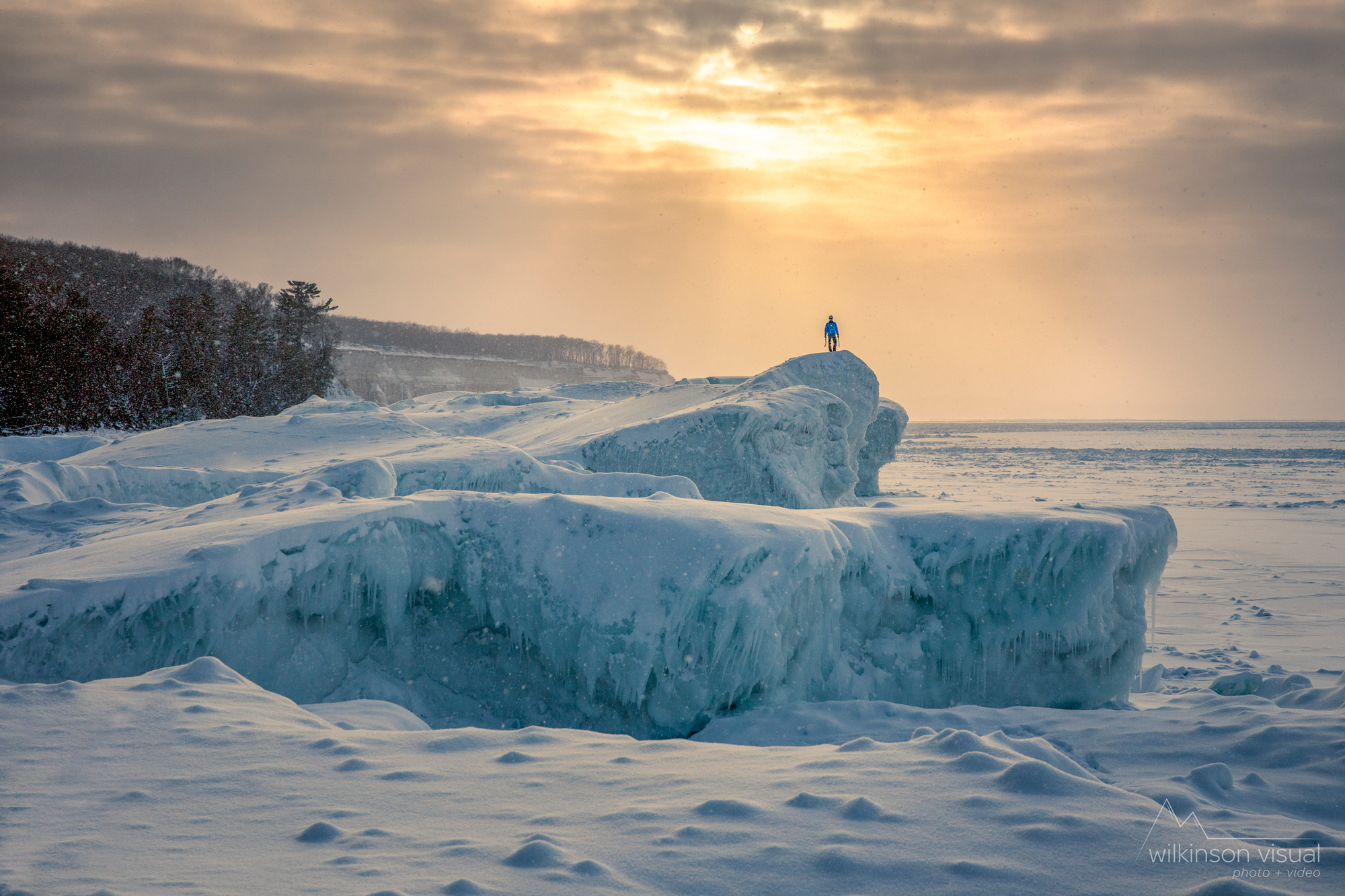 Brett Merlin walks along ice boulders in Northern Michigan.