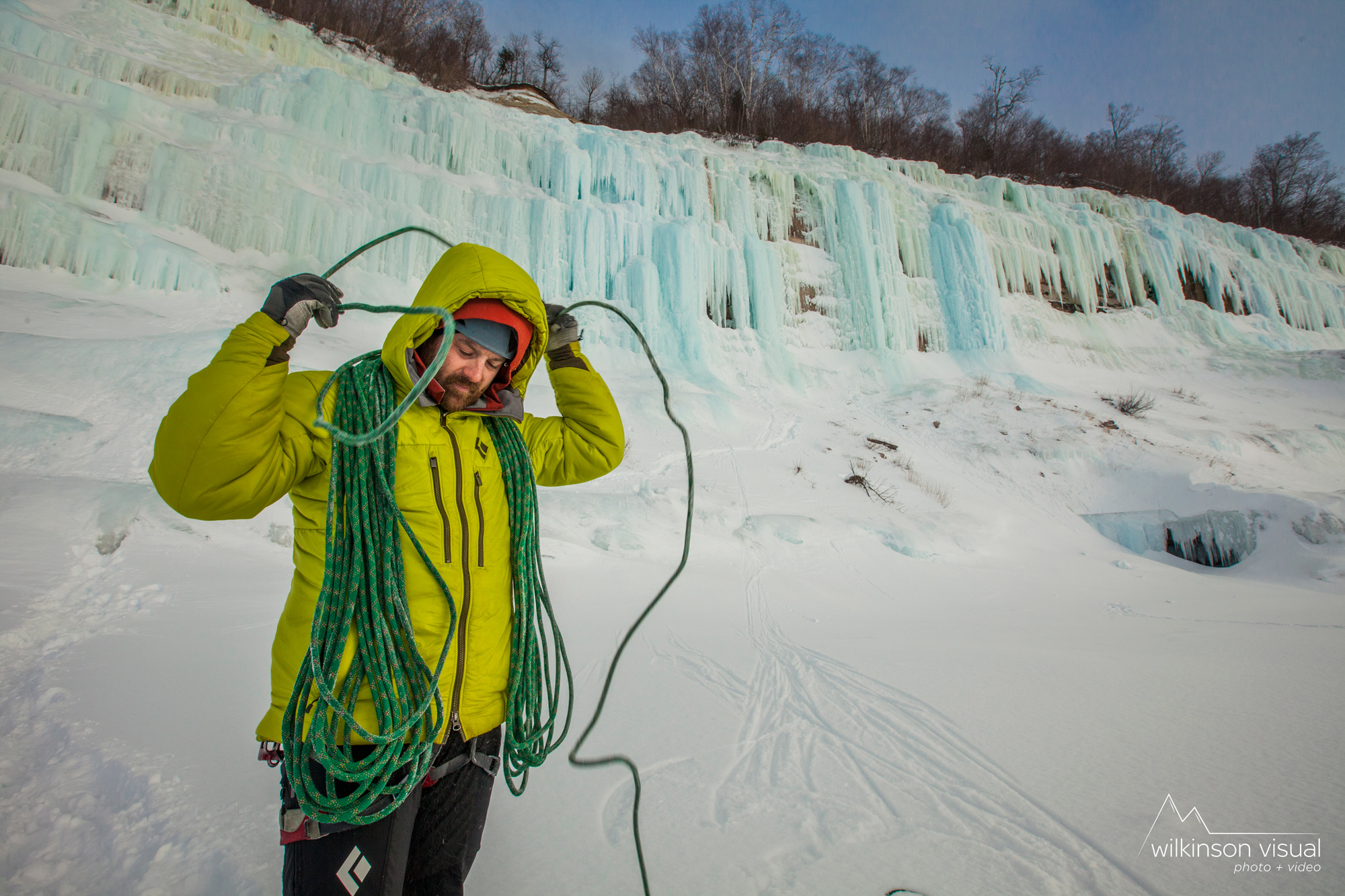 Jon Jugenheimer coils rope in front of ice climbs of Grand Island, Michigan.