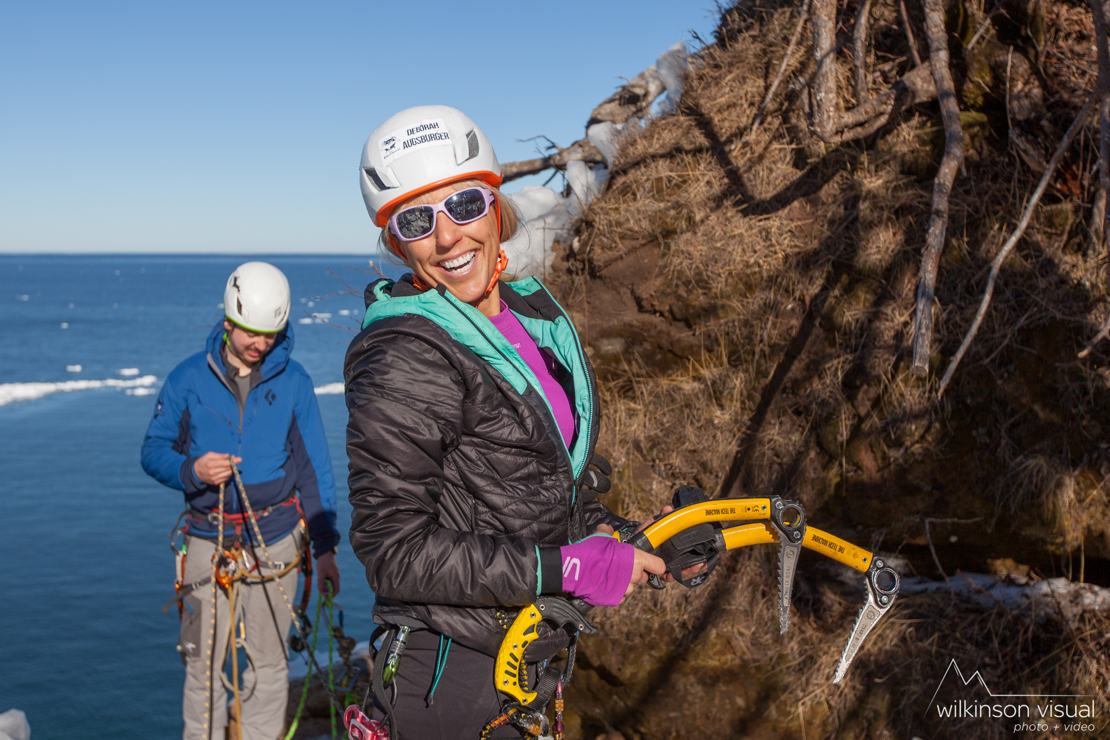 Clinic participant Deborah Augsburger is all smiles after climbing Bridal Veil at Pictured Rocks National Lakeshore, Michigan. Grivel ice tools shown.