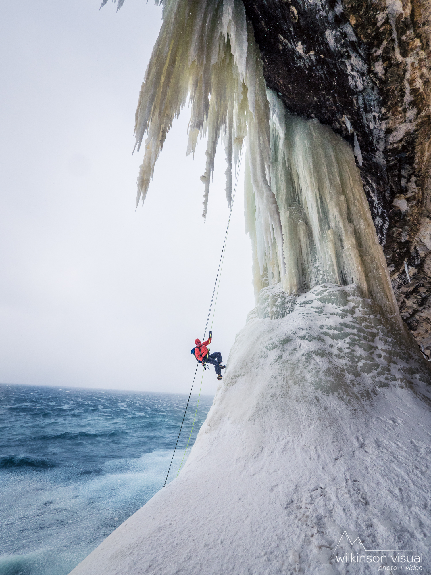 "An ice climber rappels down ""Dairyland"" with open water from Lake Superior crashing below. Pictured Rocks National Lakeshore, Michigan."