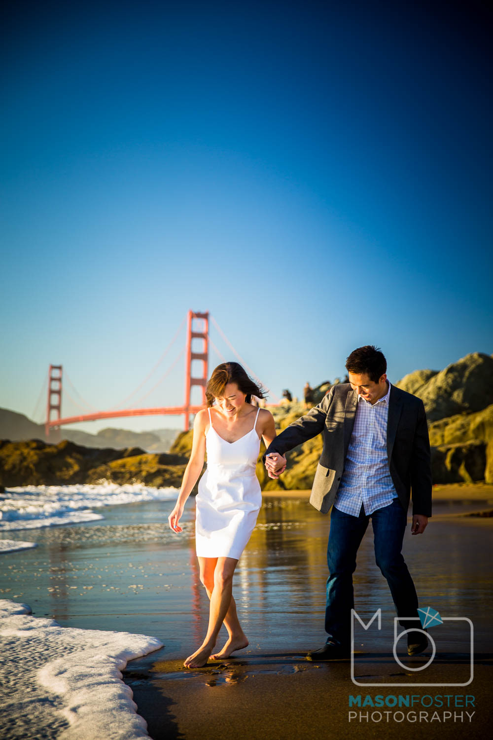 couple playing in the surf at baker beach, san francisco - engagement photography