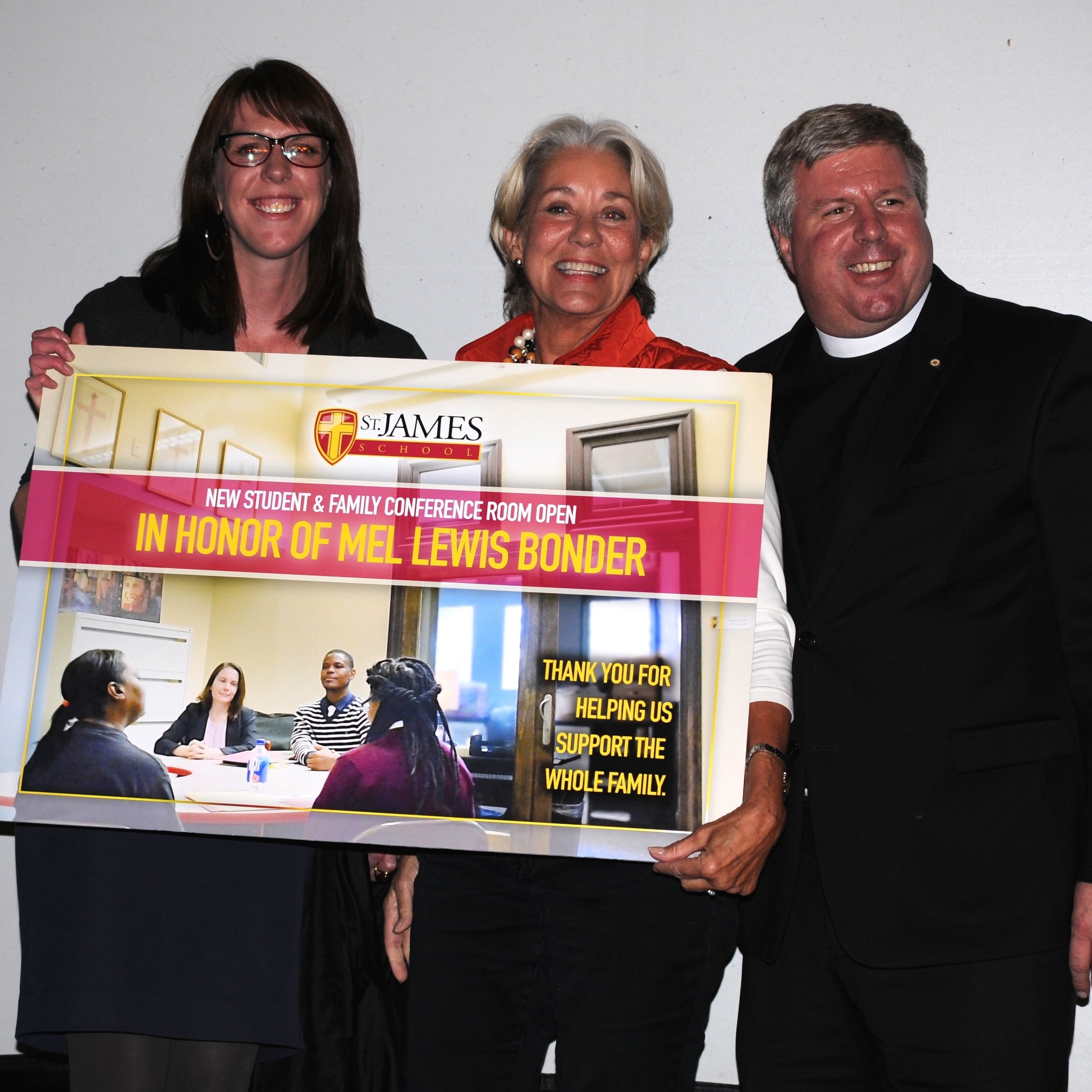 St. James School's Advancement Director Angie McCole and the school's co-founder Rev. Sean Mullen make a surprise presentation to ECHOES co-founder Mel Bonder, announcing that a new student/family conference room will be named in her honor.