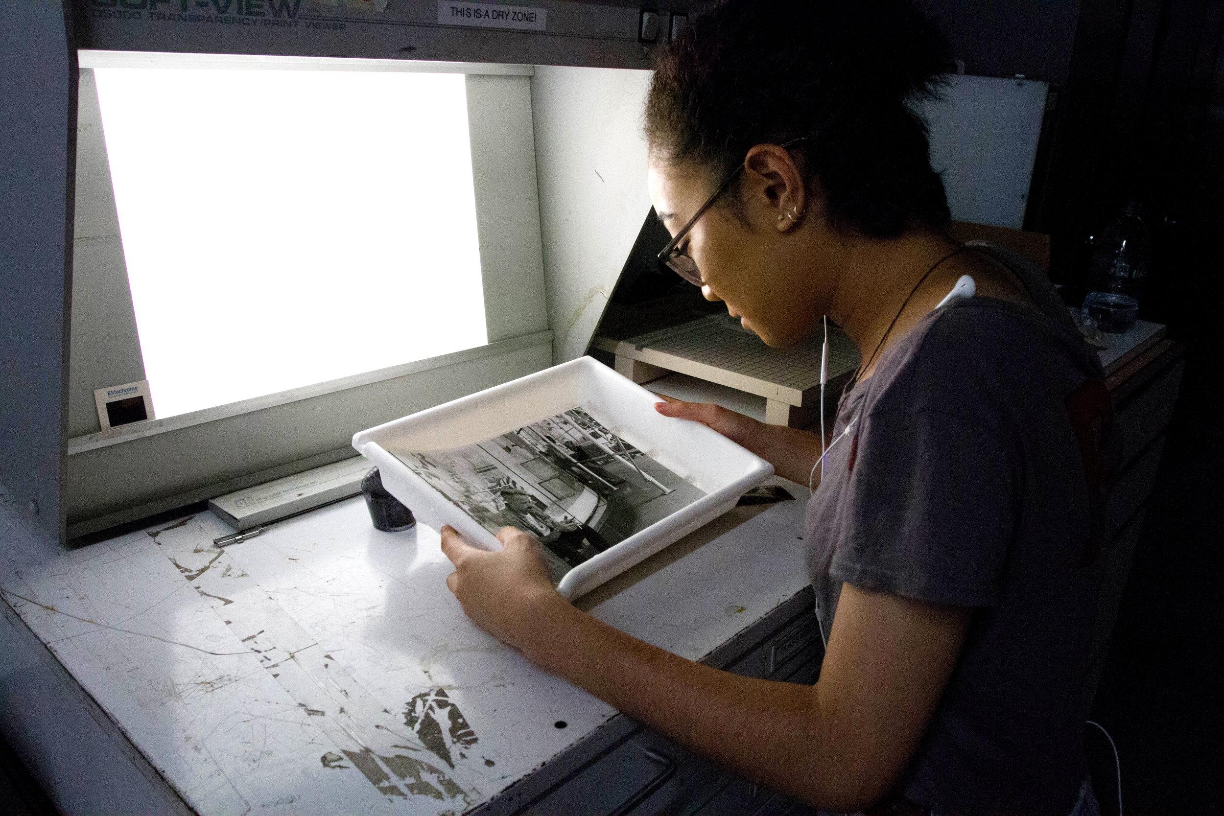 High school intern Maya inspects a freshly made B&W print