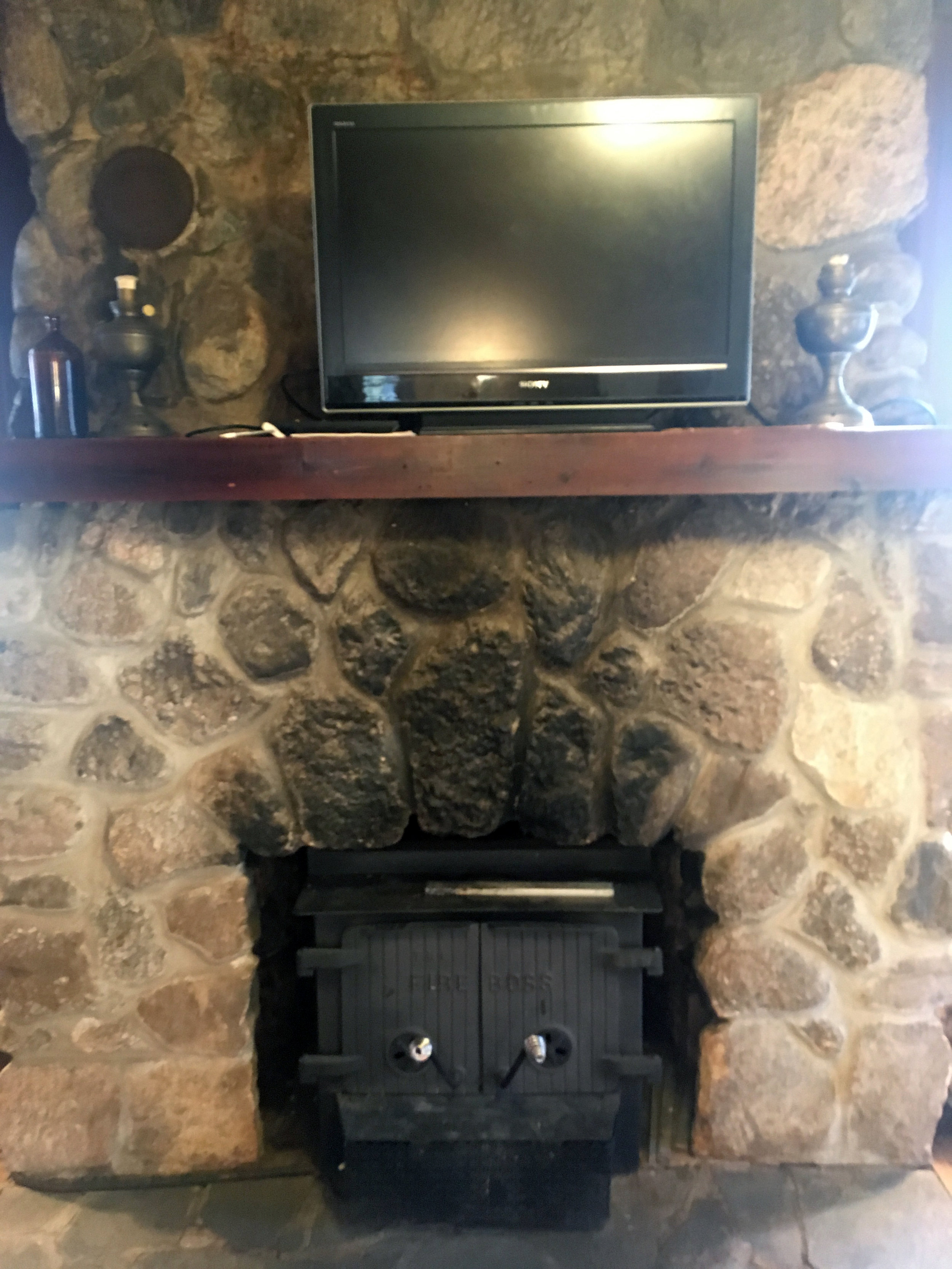 Fireplace has a working wood stove. Flat screen TV has an HDMI cable that can be plugged into computers for streaming.