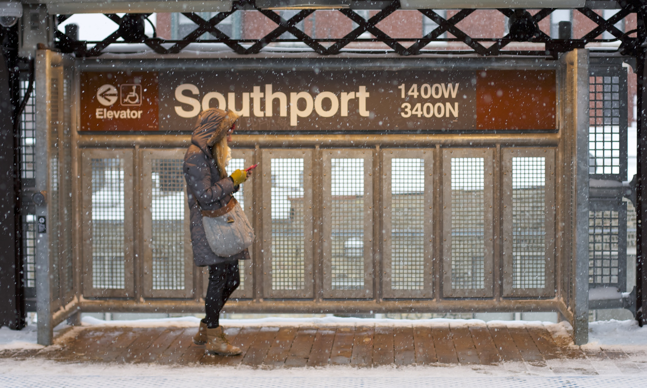 A woman check her phone in the Southport Station warming box as the snow falls