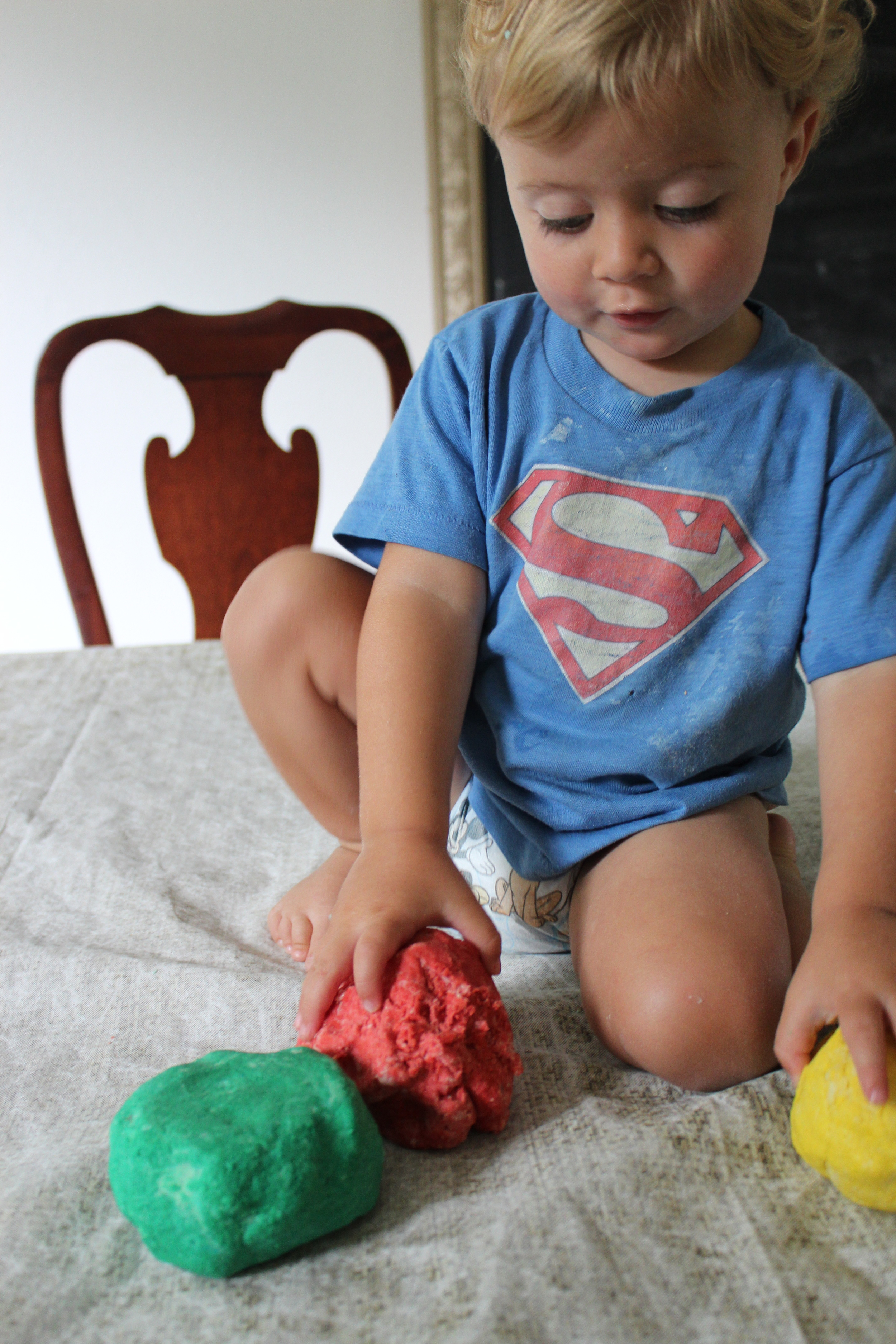 Diaper baby modeling the playdough.