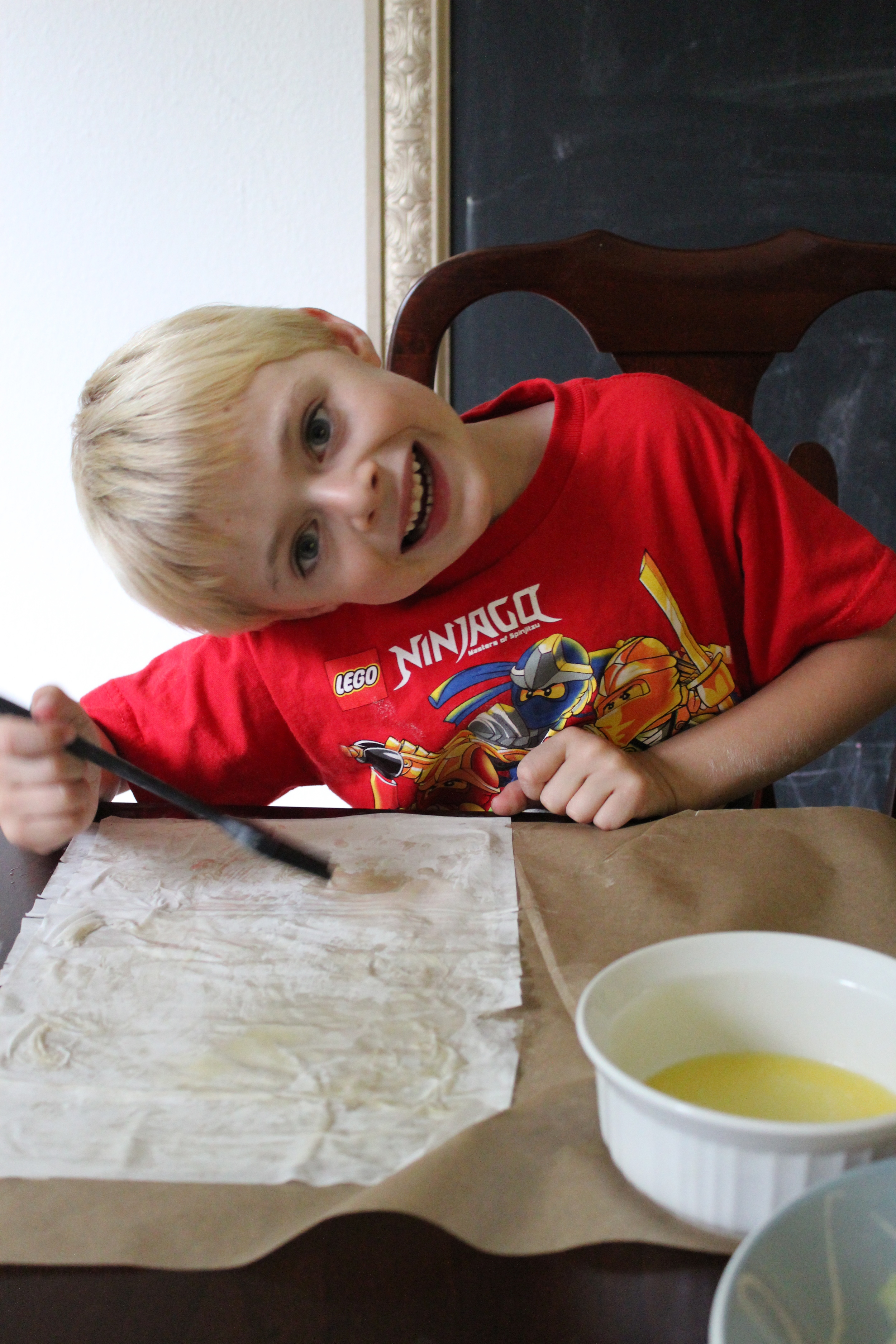 My oldest has lately been extra silly whenever the camera comes out. Here he is spreading butter on the dough.