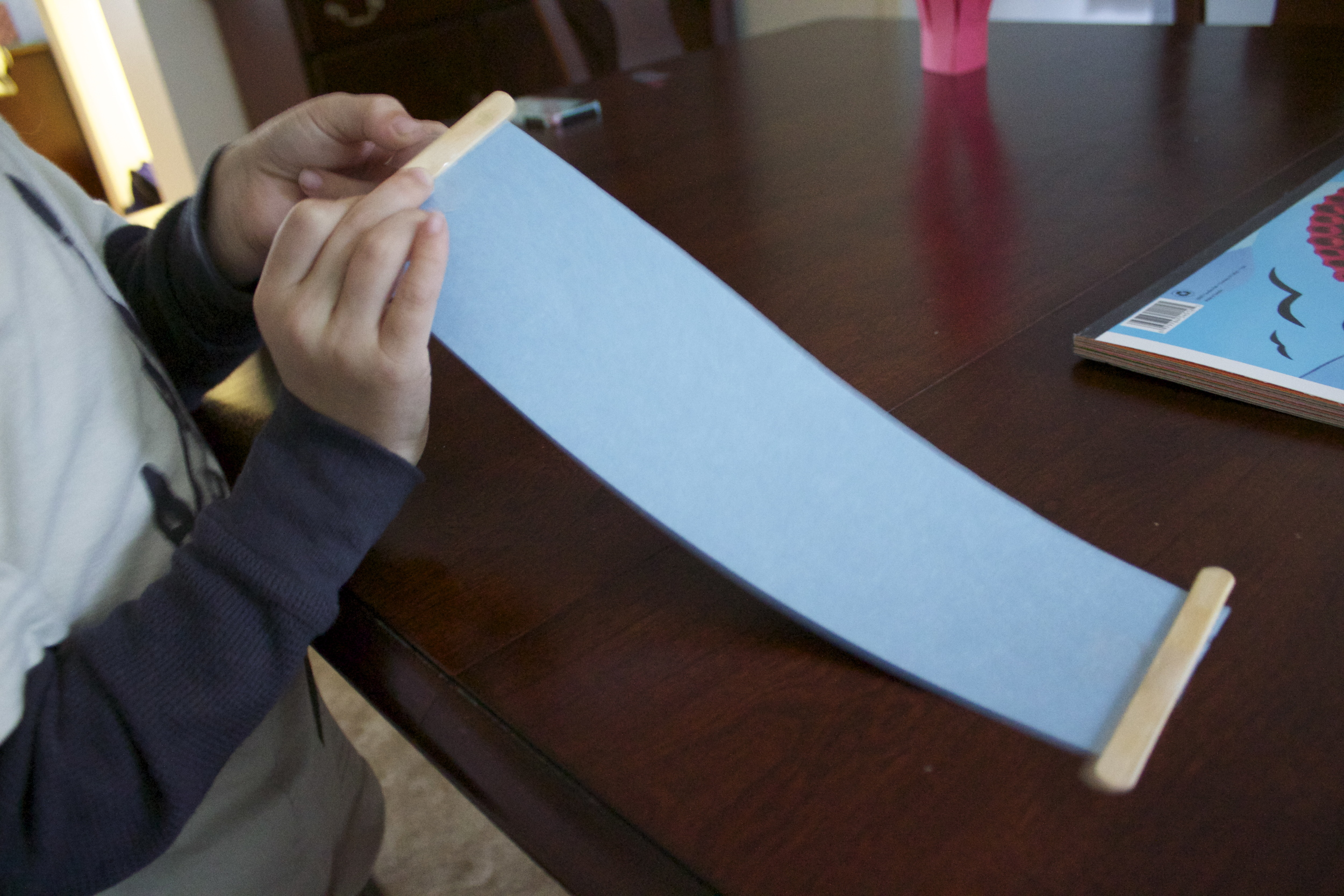 Taping the sticks to the paper.