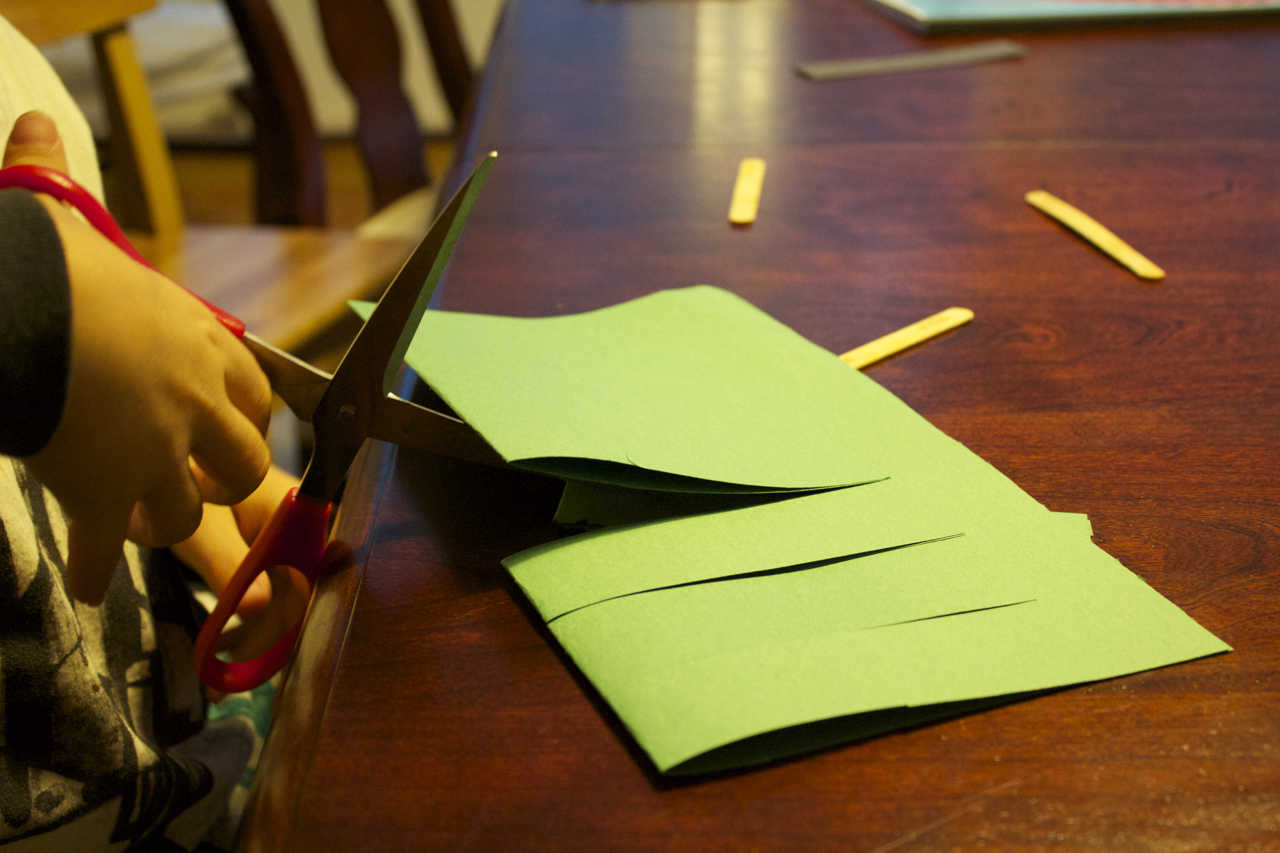 Cut slits into the paper from folded end until about an inch to the open end.