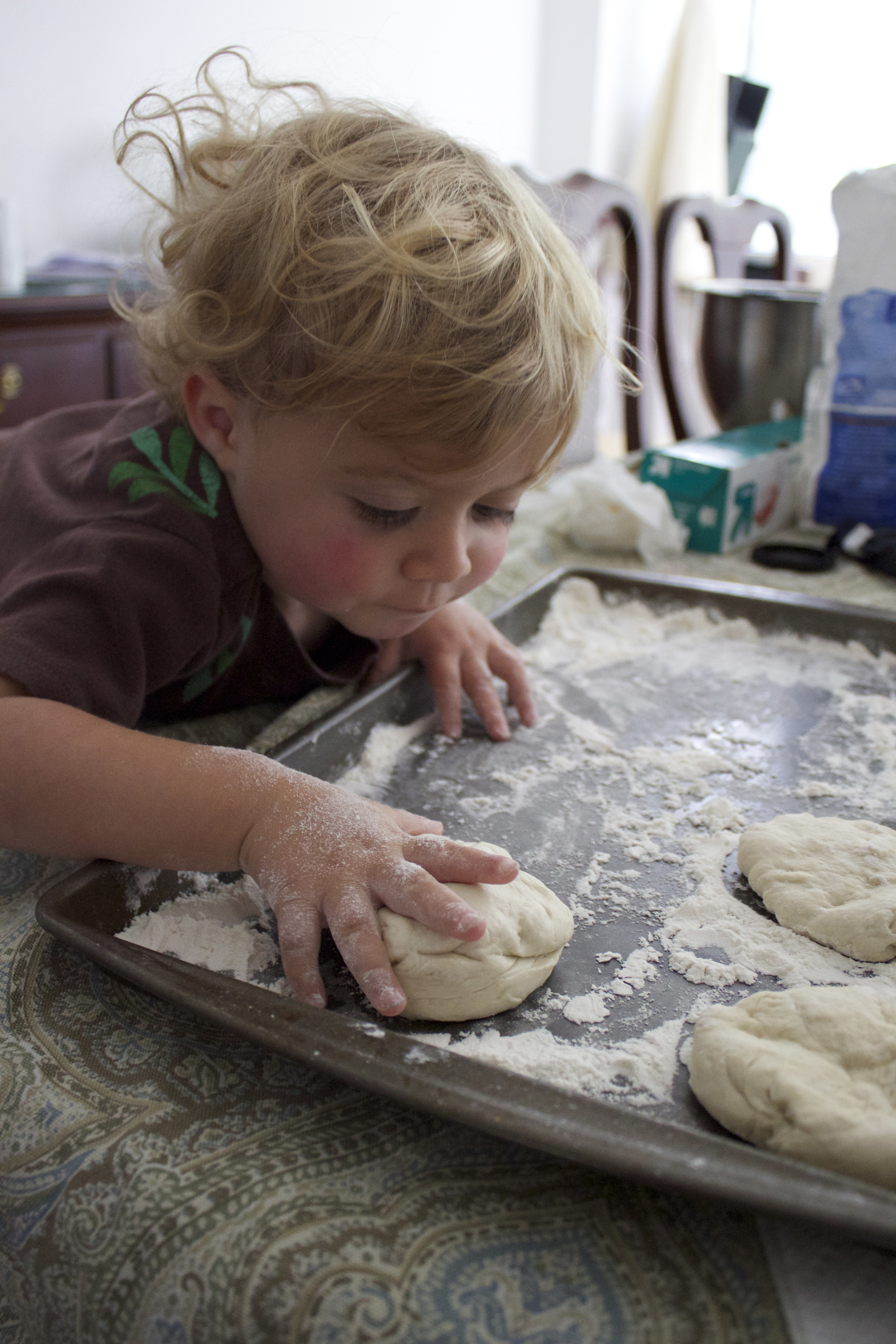Happily patting the dough down.