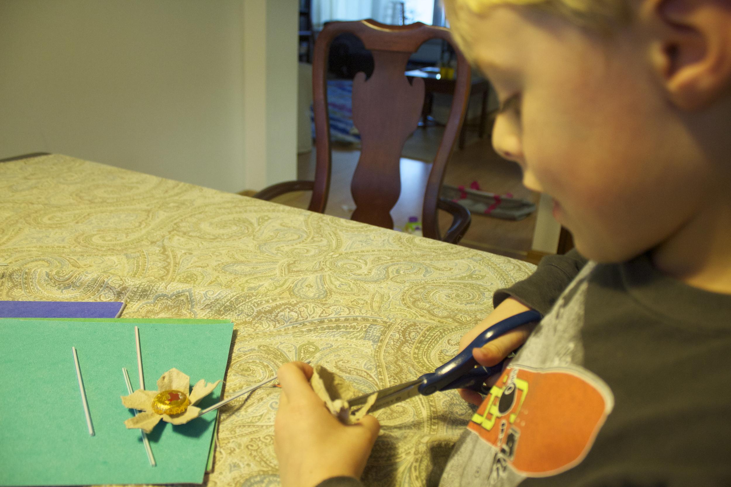 Cutting the egg carton to create the petals.