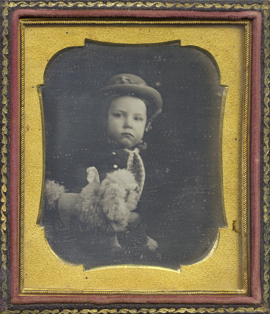 Portrait of a Young Child Wearing a Hat and Holding a Toy Poodle