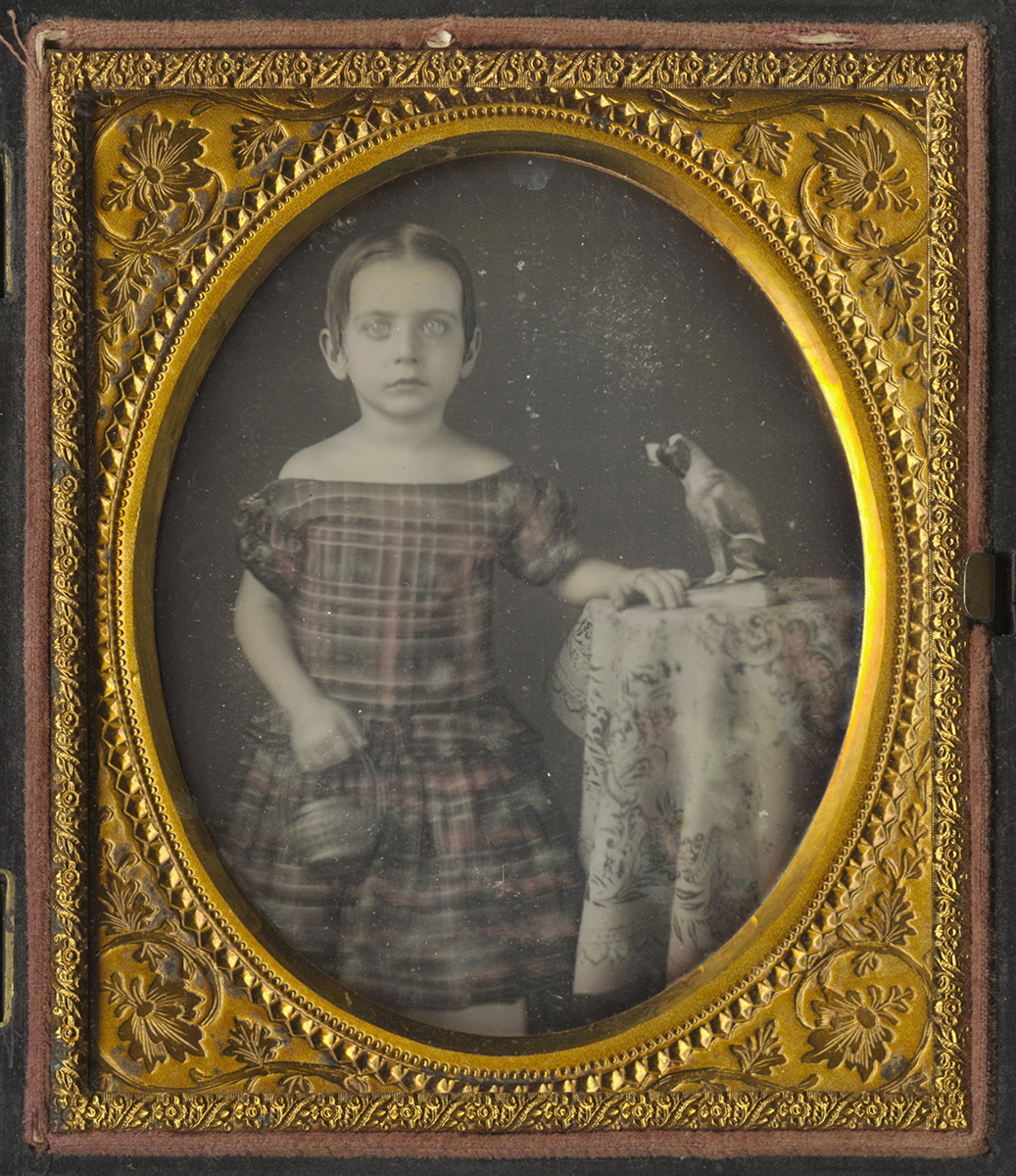 Portrait of Young Girl Holding Straw Basket - Statue of a Dog on Table Beside Her