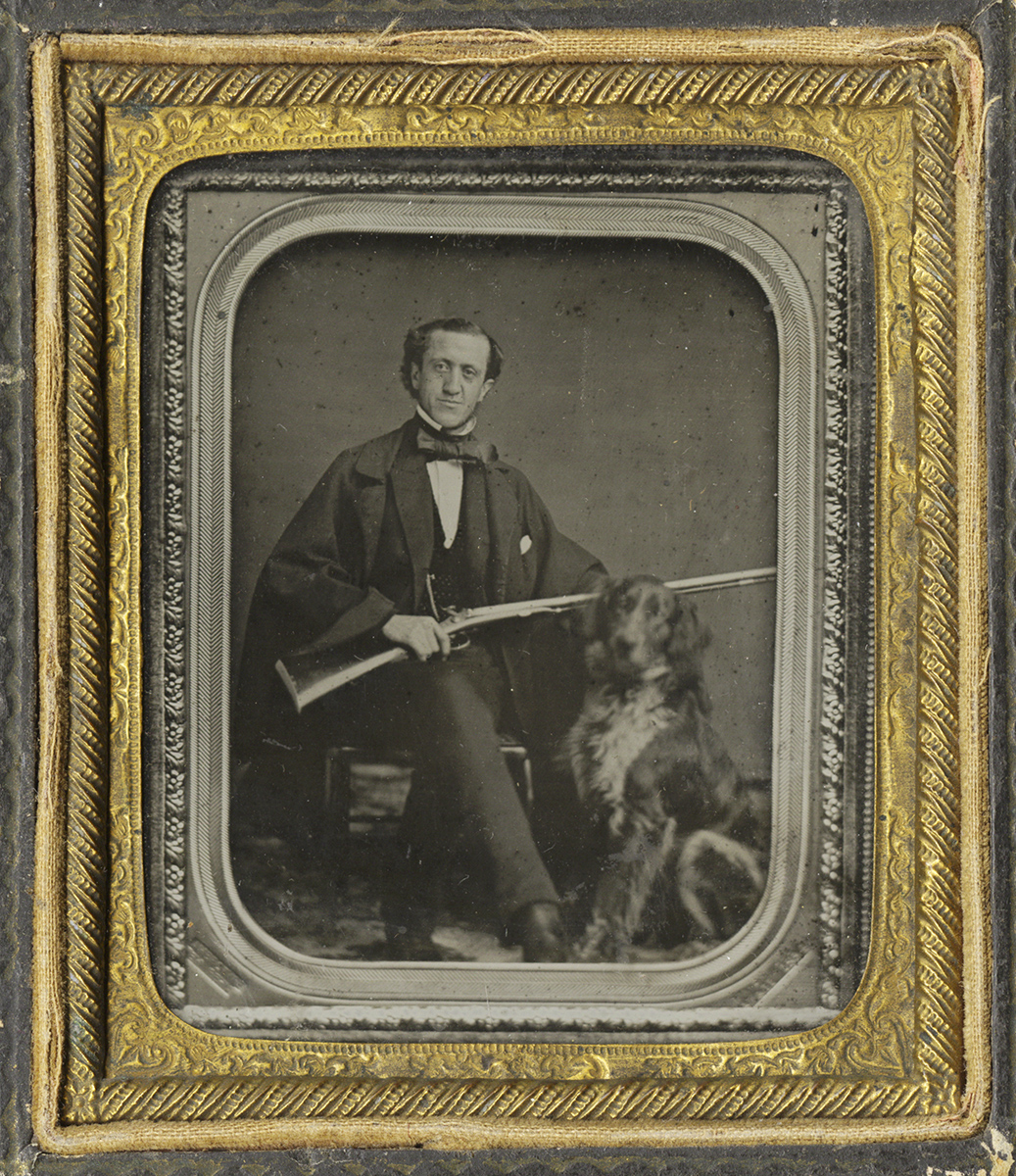 Man Holding A Rifle Seated Next to His Dog
