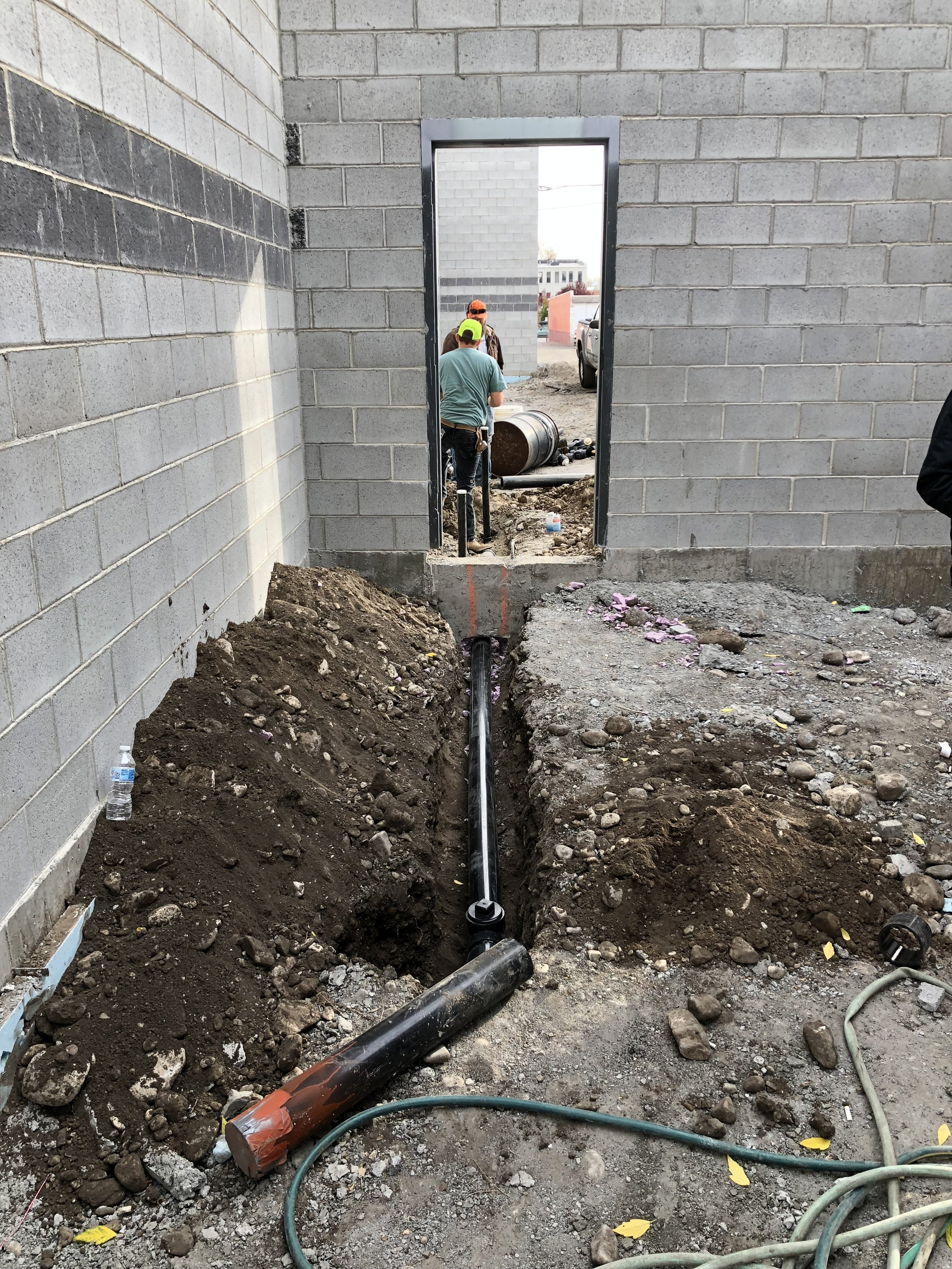 Today the underground work started. This photo shows the plumbers tying into the new sewer line from the new janitor closet and bathroom. They finished most of their work today so the rest of the week should be the electricians who have a lot to do. We will also be running conduit to carry lines from the house into the studios and between the studios, as well as the lines that go from the racks to the consoles and the machine rooms.