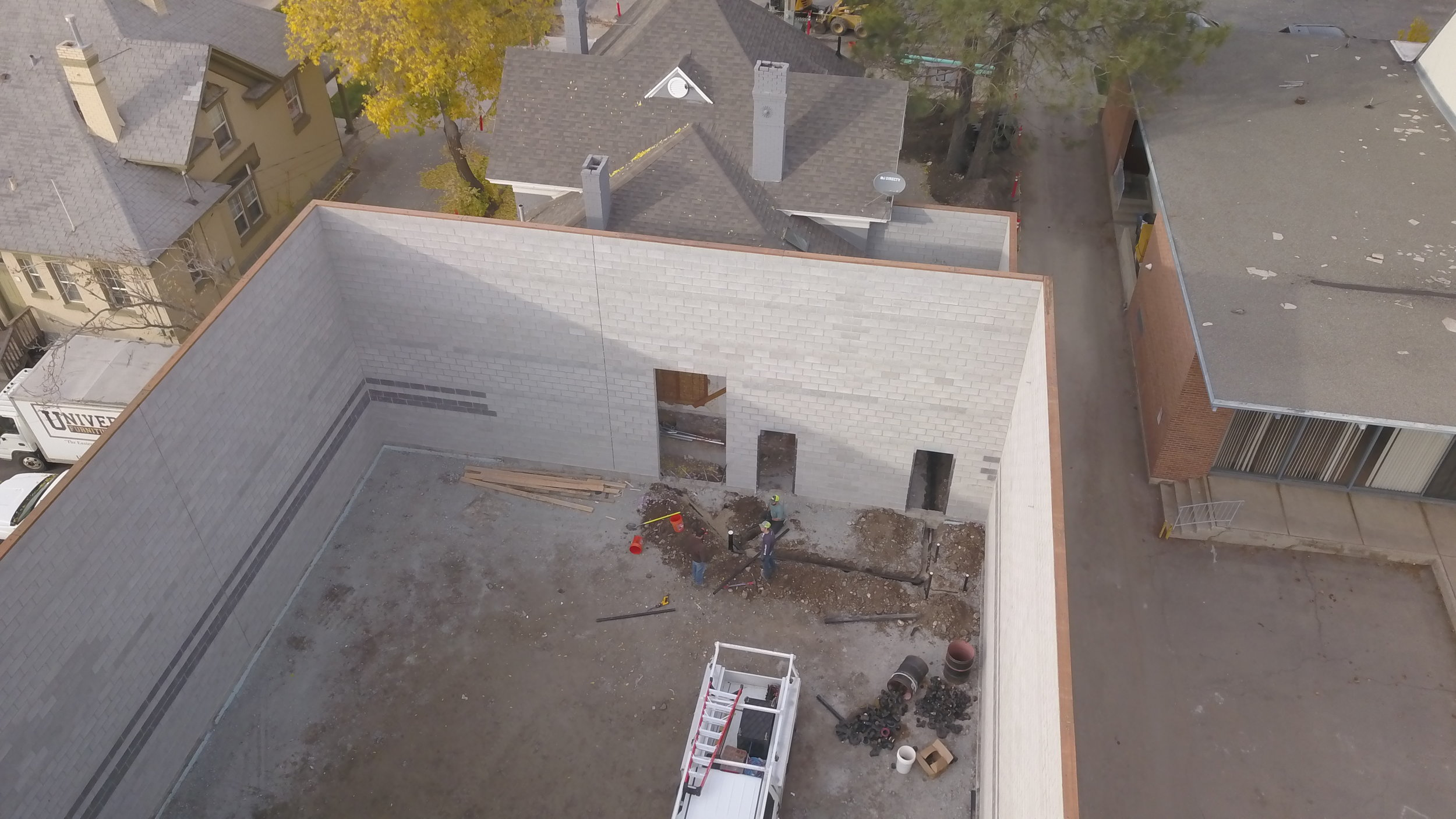 Plumbers getting the drain lines installed, door on the right is lobby into the janitor closet, door on the left is lobby into the bathroom. the large opening is lobby into the hallway which will run between studios.